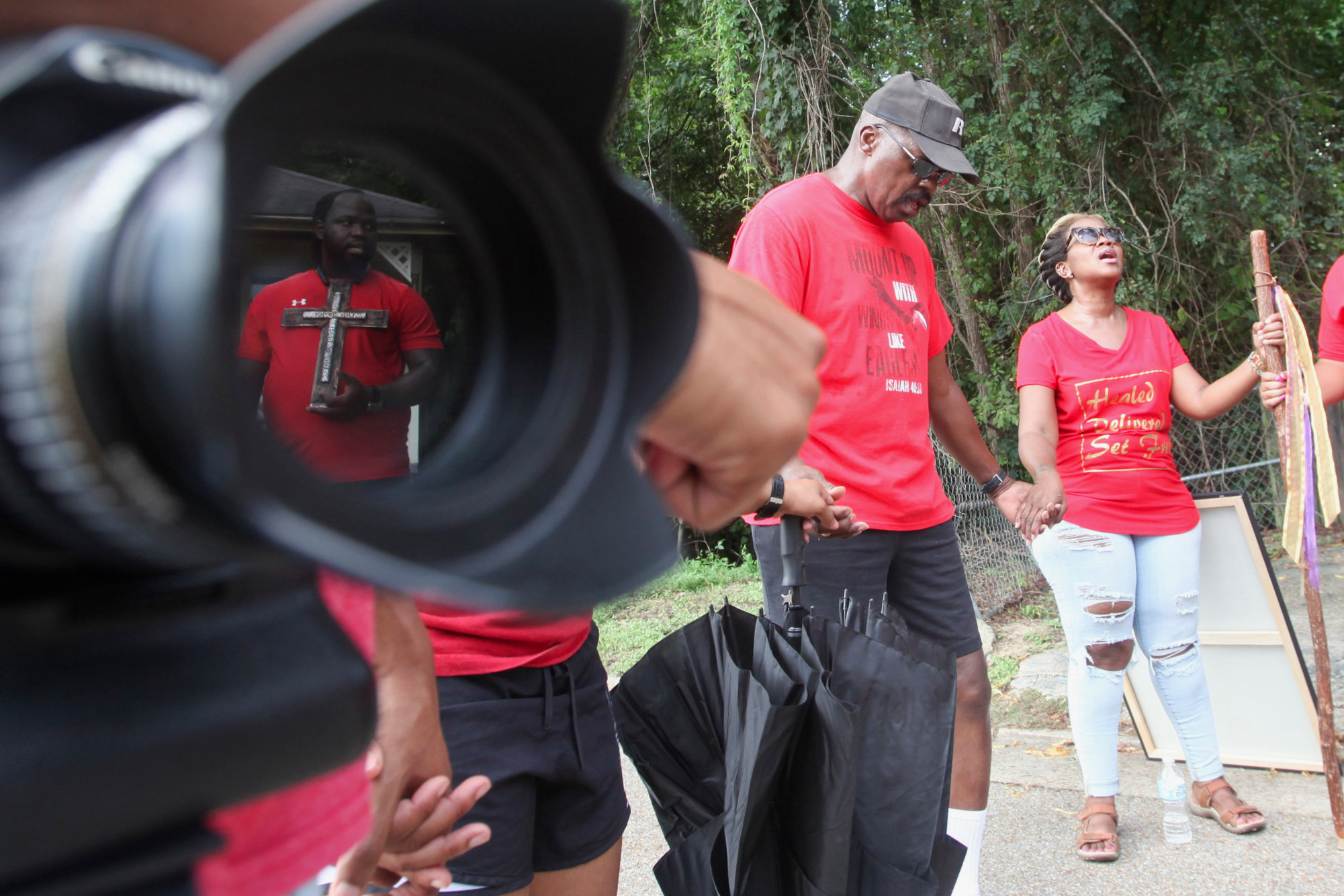 Lamont Rogers is reflected in the lens of a camera as he holds a cross during prayer at the intersection of Lane and Togo street in the Unity Prayer Walk in Marcus Bottom Saturday. Parishioners walked, prayed and sang their way to a gathering at the Ken Karyl playground.  (Courtland Wells/The Vicksburg Post)