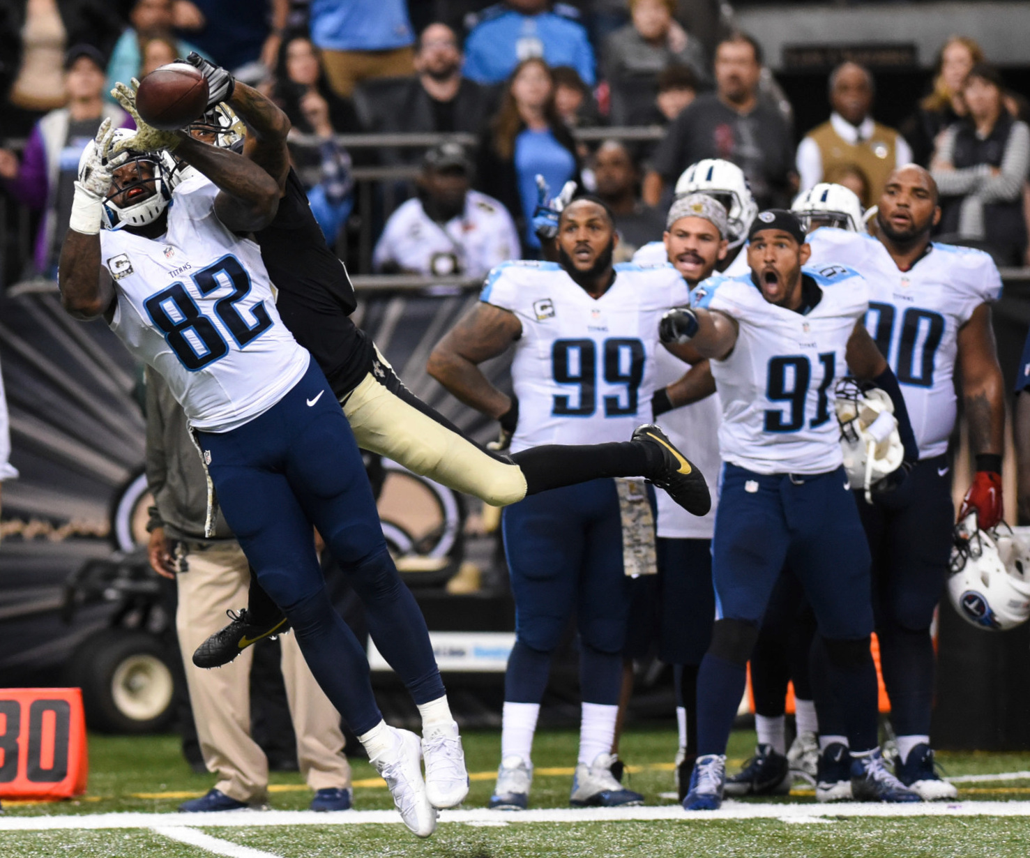 Titans tight end Delanie Walker (82) goes up for a pass with a Saints defender behind him during the game at the Mercedes-Benz Superdome in New Orleans. Sunday Nov. 8, 2015. The Saints fell to the Titans 34-28 in overtime.