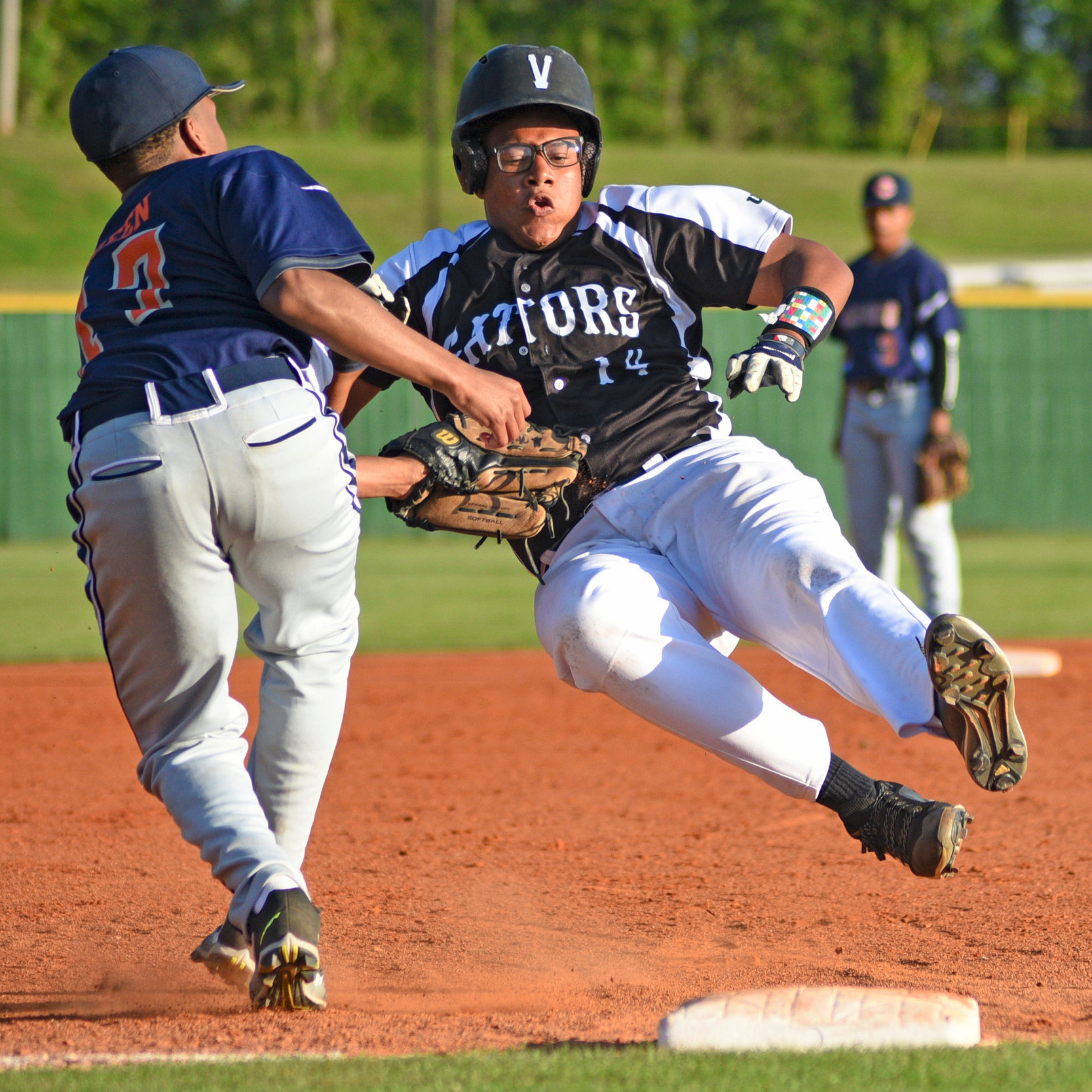 Vicksburg's Jordan Miller (14) is tagged out by Callaway's Kemorian Herring (17) while sliding into third base during their game Tuesday at Bazinsky Field. The Gators defeated the Chargers 17-7. (Courtland Wells/The Vicksburg Post)