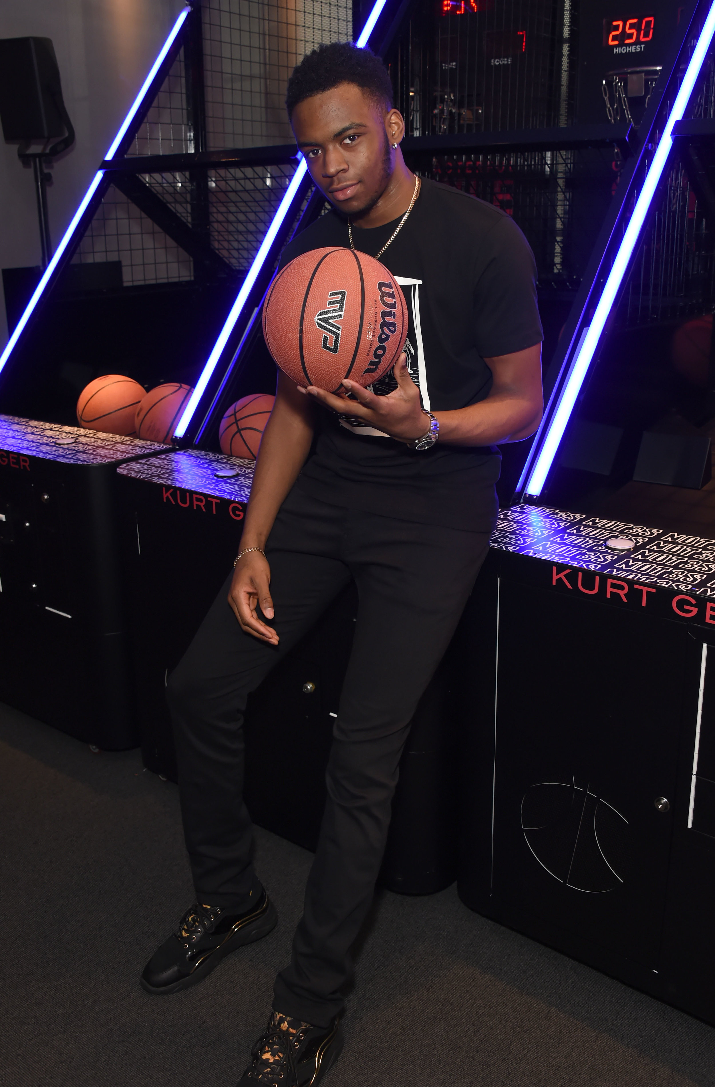 Not3s at the Kurt Geiger Event holding a basketball