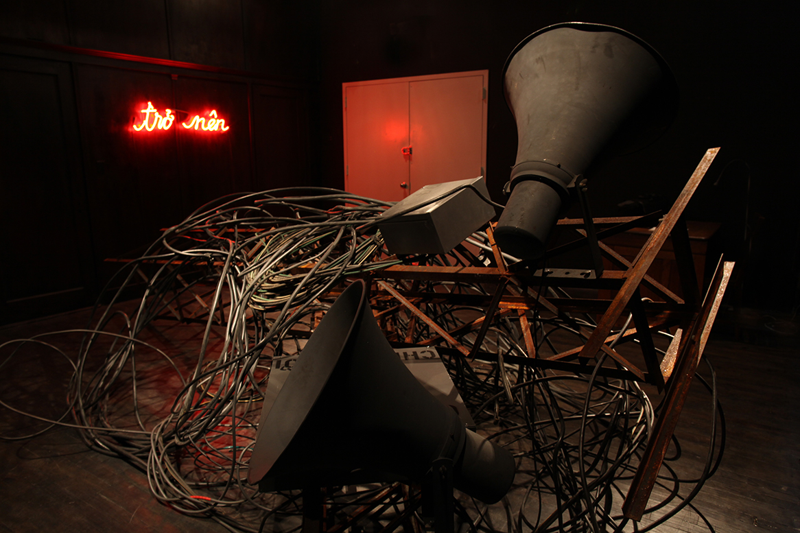 "To Speak A Language (2012) Angle iron, electric wires, public address speakers, metal boxes, found book, neon light, amplifier, sound 168 "" x 120"" x 24"" Installation view at Agape Enterprise Courtesy the artist"