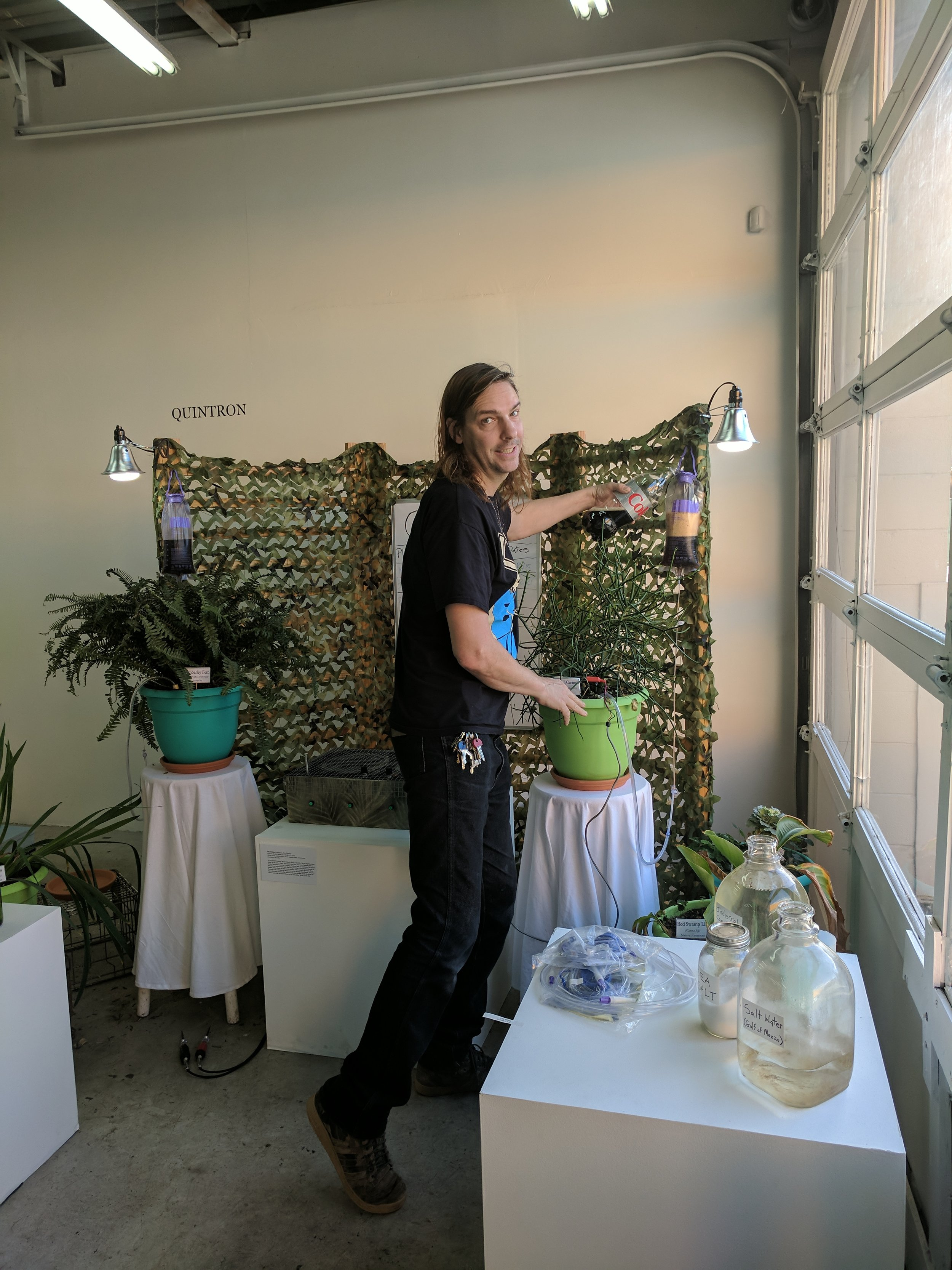 "Quintron Tending to Plants on his ""Organic Matter Death Clock,2017"" at P.4 Welcome Center"