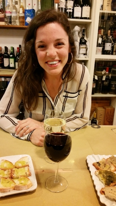 Erica sipping on wine in a wine shop in Florence.