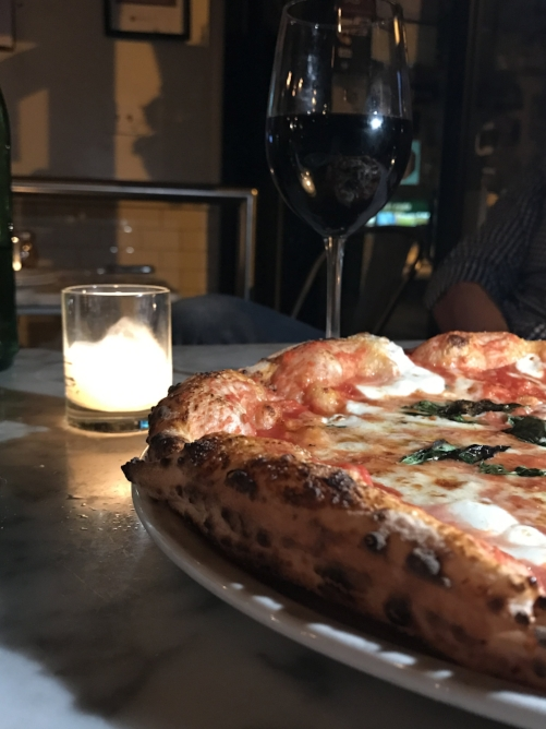 M  argherita pizza and a glass of Montepulciano red from Motorino Pizzeria.
