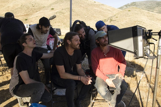 Director Carlos Puga and the crew watch a take in the desert.