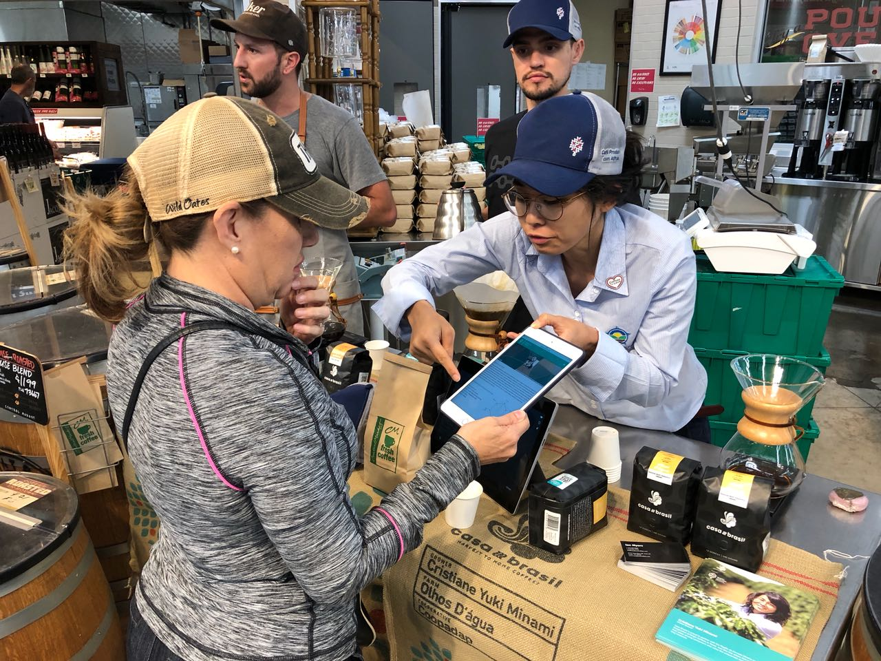 Reading the QR code that shows the coffee traceability up to the producer and farm level to a customer at Central Market