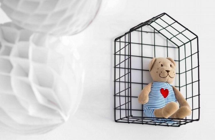 teddy bear on shelf and white wall