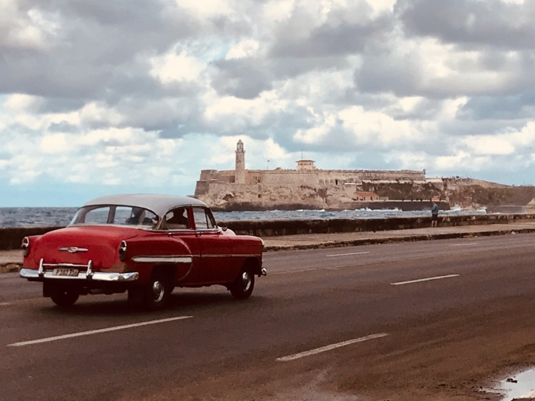 Car driving along El Malecón with El Morro in the background.