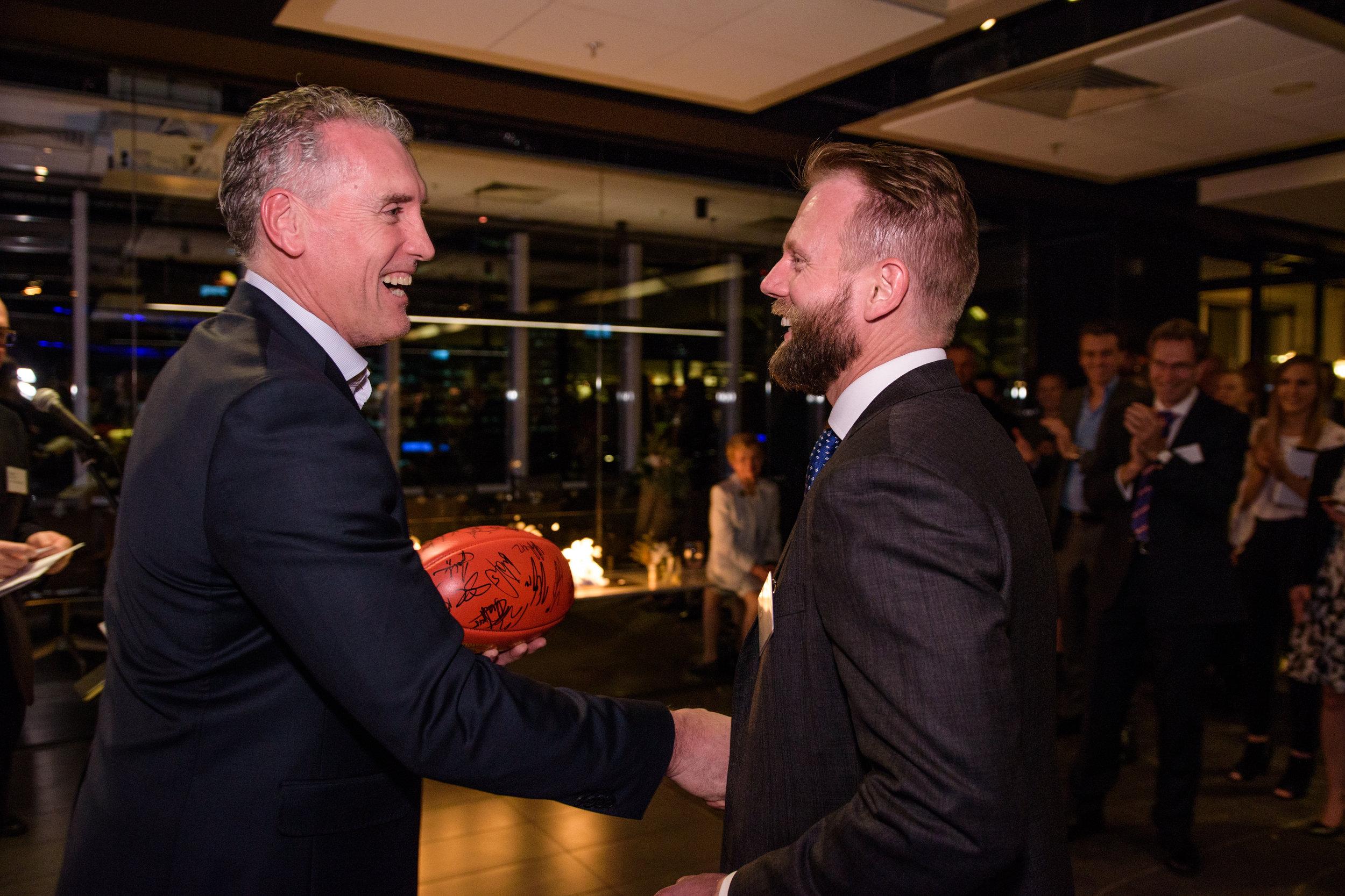 Darren Baxter congratulates Matt Strauch on winning the football signed by the Western Bulldogs Premiership players