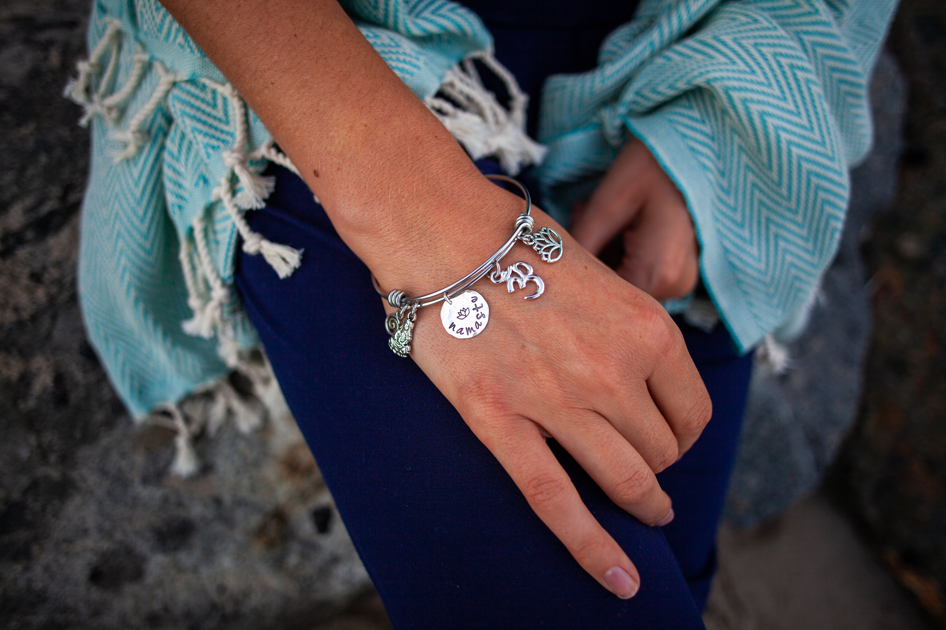 Fig 9. Namaste charm bracelet by Tracy Tayan designs photographed on the rocks on Venice Beach. Turkish towel by Together Textiles.