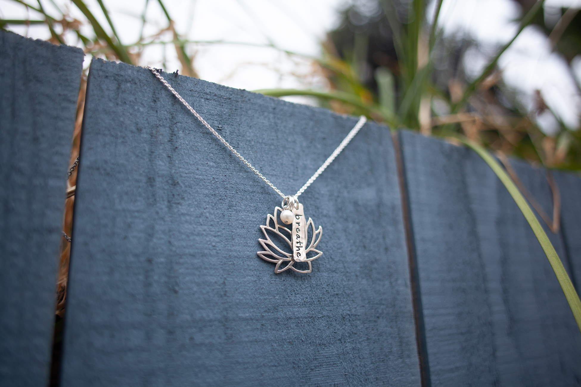 Fig. 10 Breathe necklace by Tracy Tayan designs on a blue fence in Venice, California.