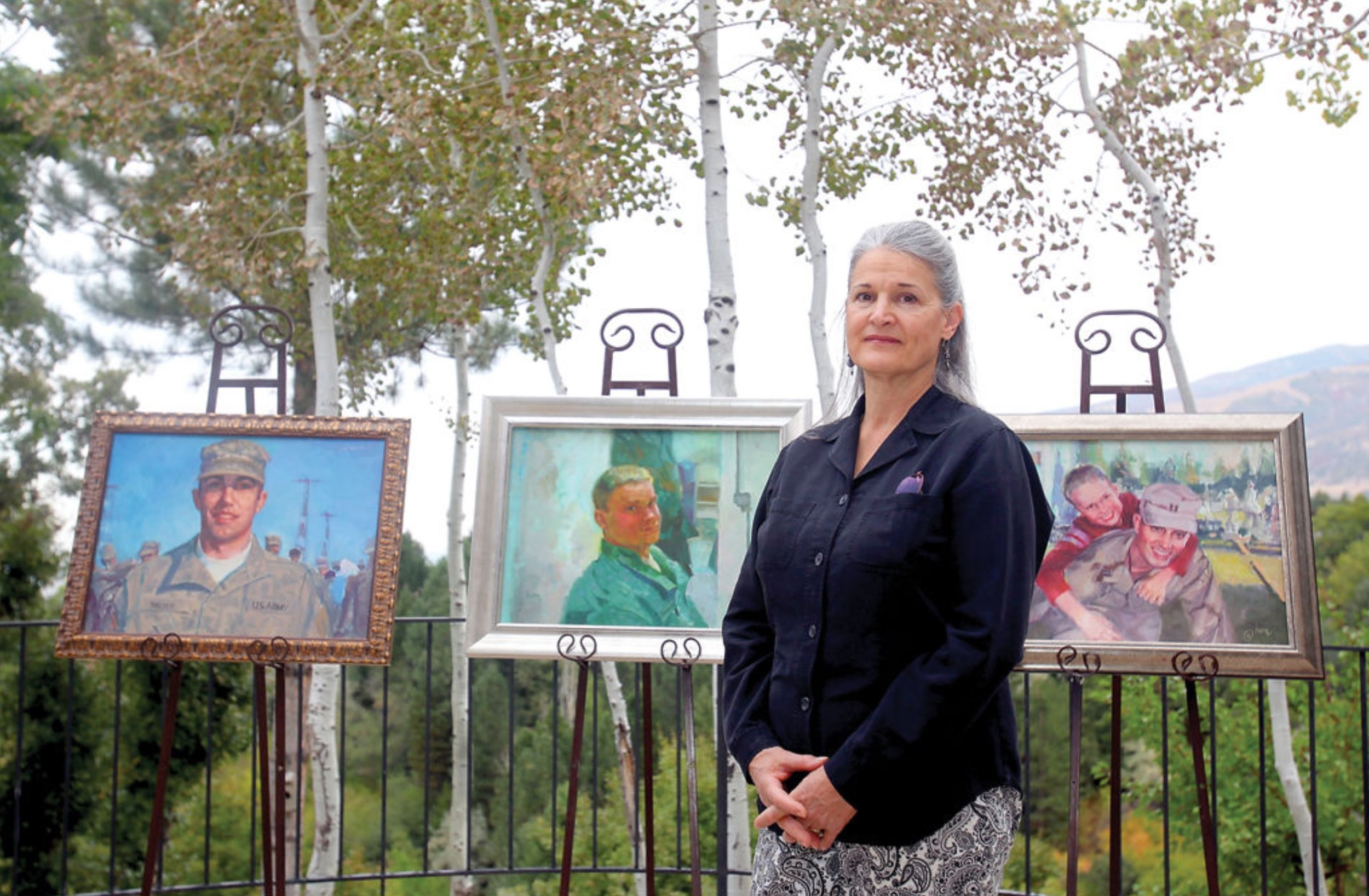 Anne Marie Oborn with some of the 250 portraits she has painted for the families of fallen members of the military. (Photo courtesy of the Standard Examiner)