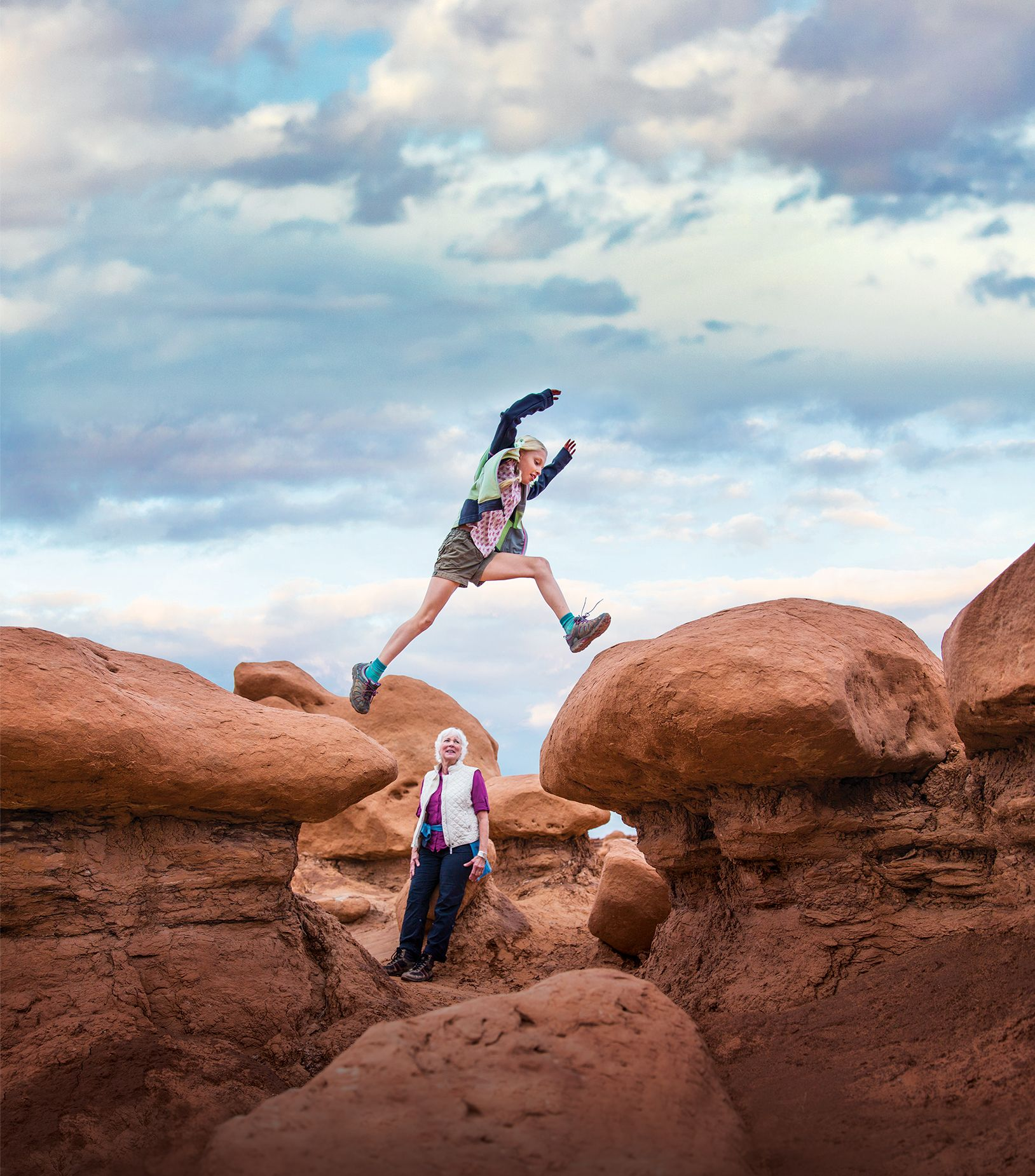 A photo of a young girl jumping from rock to rock