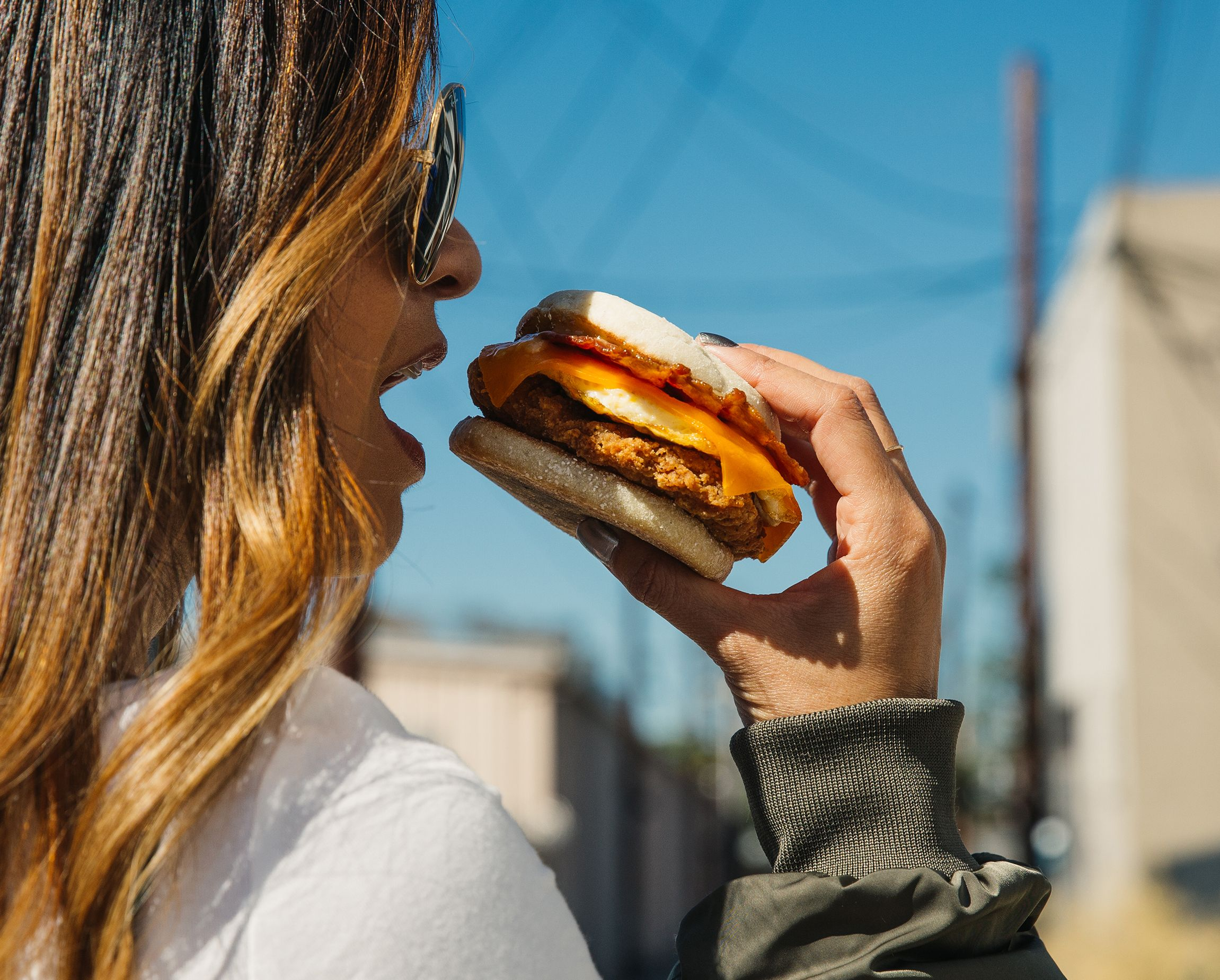 Girl eating a chicken and egg sandwich.