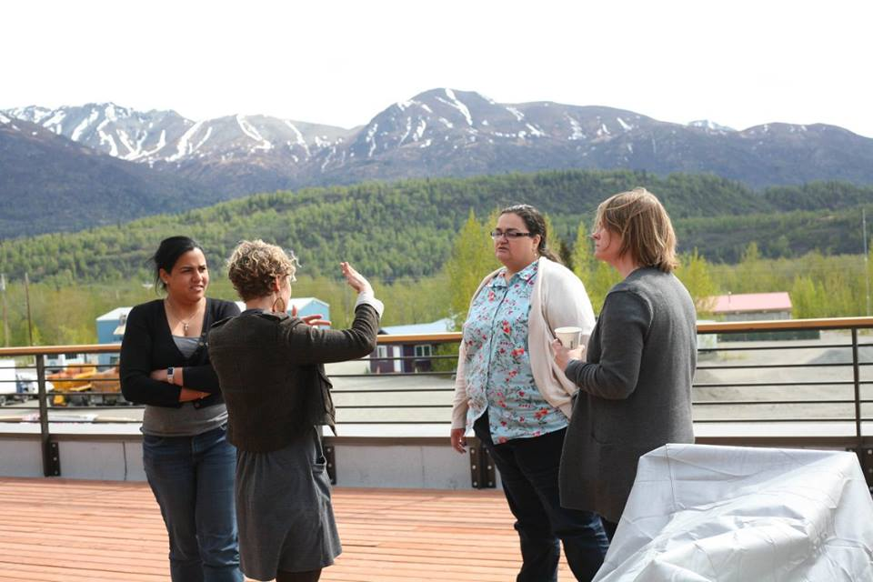 Alaska Resilience Initiative (ARI) Director Laura Norton-Cruz talks with MSW intern Claudia Maria-Mateo, ARI Steering Committee Co-Chair Lisa Wade, and Health Federation of Philadelphia project manager, Clare Reidy. on the deck of the Sutton health clinic, overlooking areas for future construction of wellness facilities.