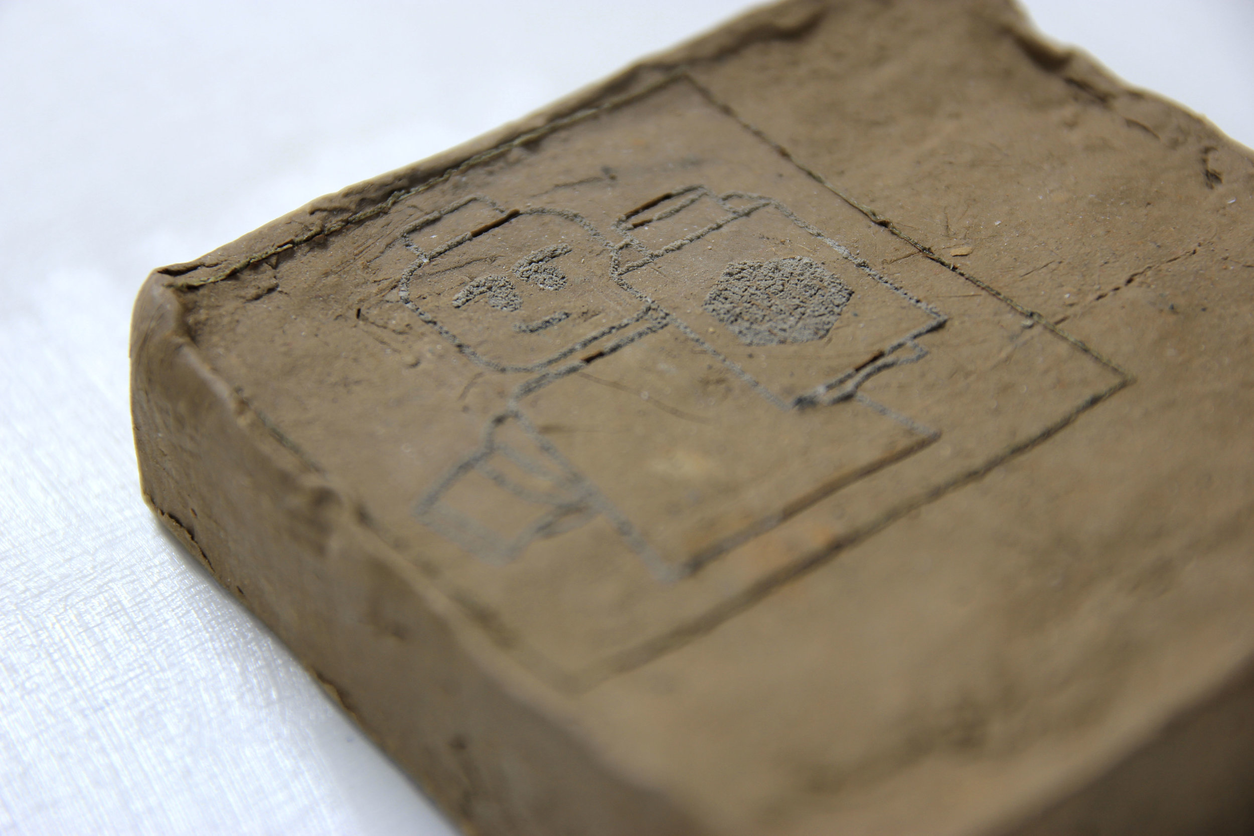 Laser etching onto dug-up mud, likely with a reasonably high clay content (and yes that is a LEGO figure).