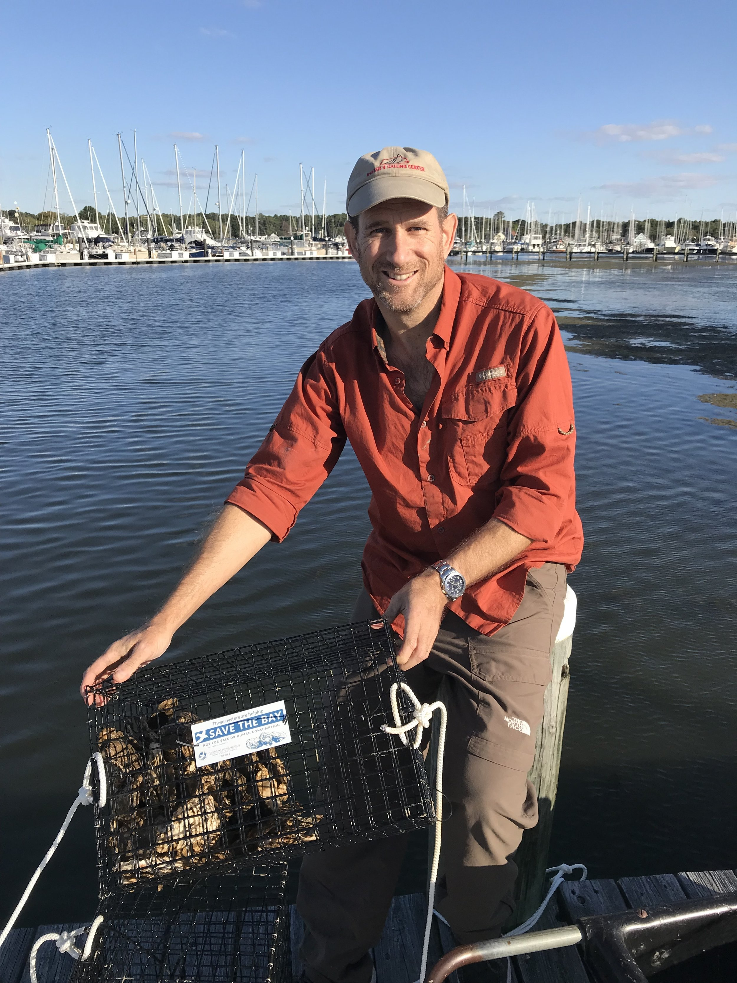 - Captain Davis Jones getting ready to place Oysters in the water off our dock.