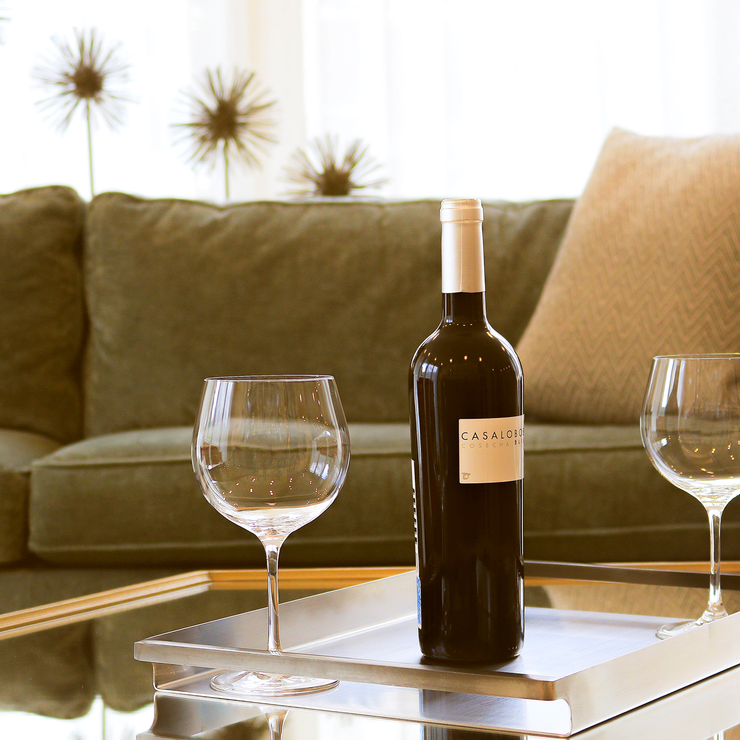 Bottle of wine and two glasses on coffee table, couch in background