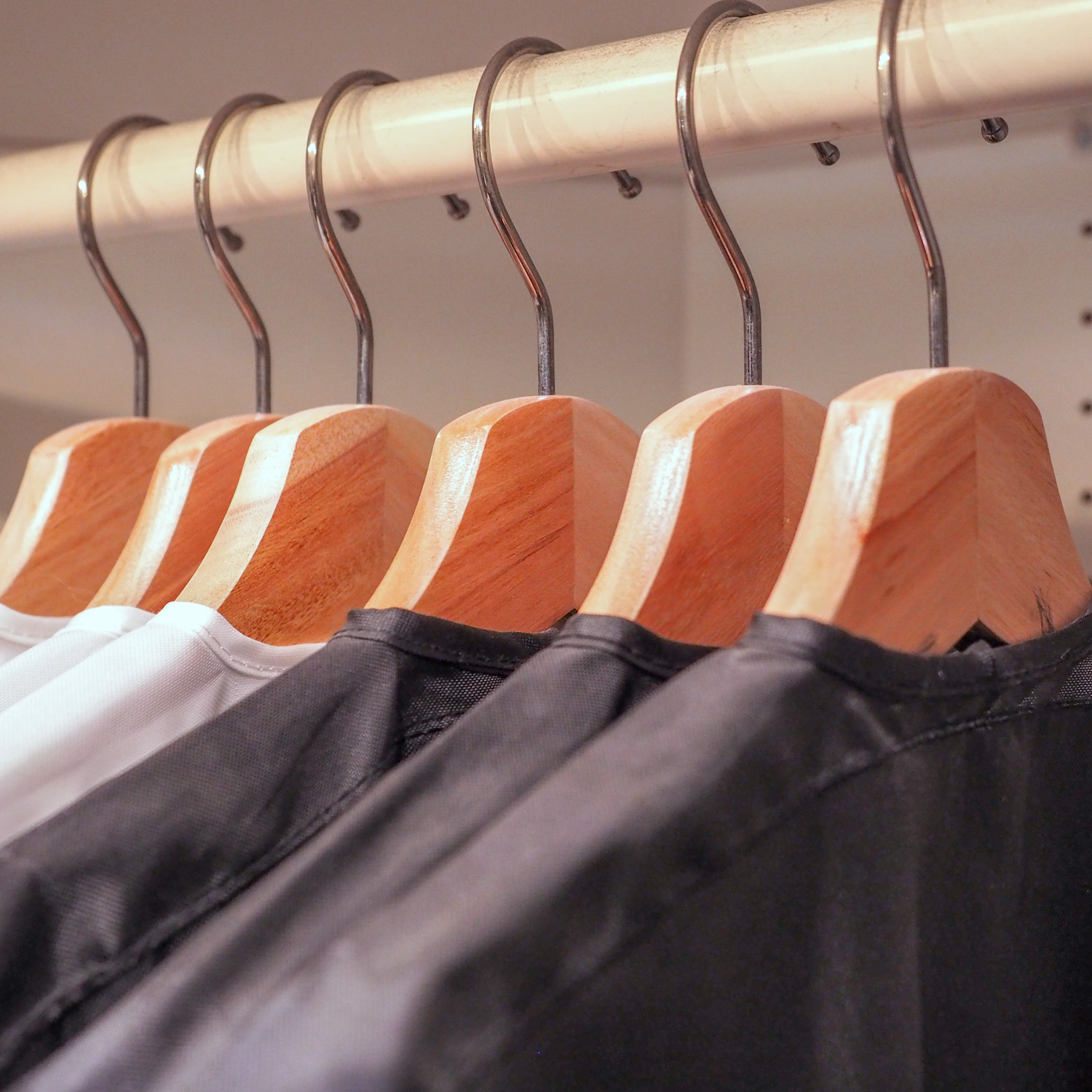 Close-up view of clothes on wooden hangers in closet