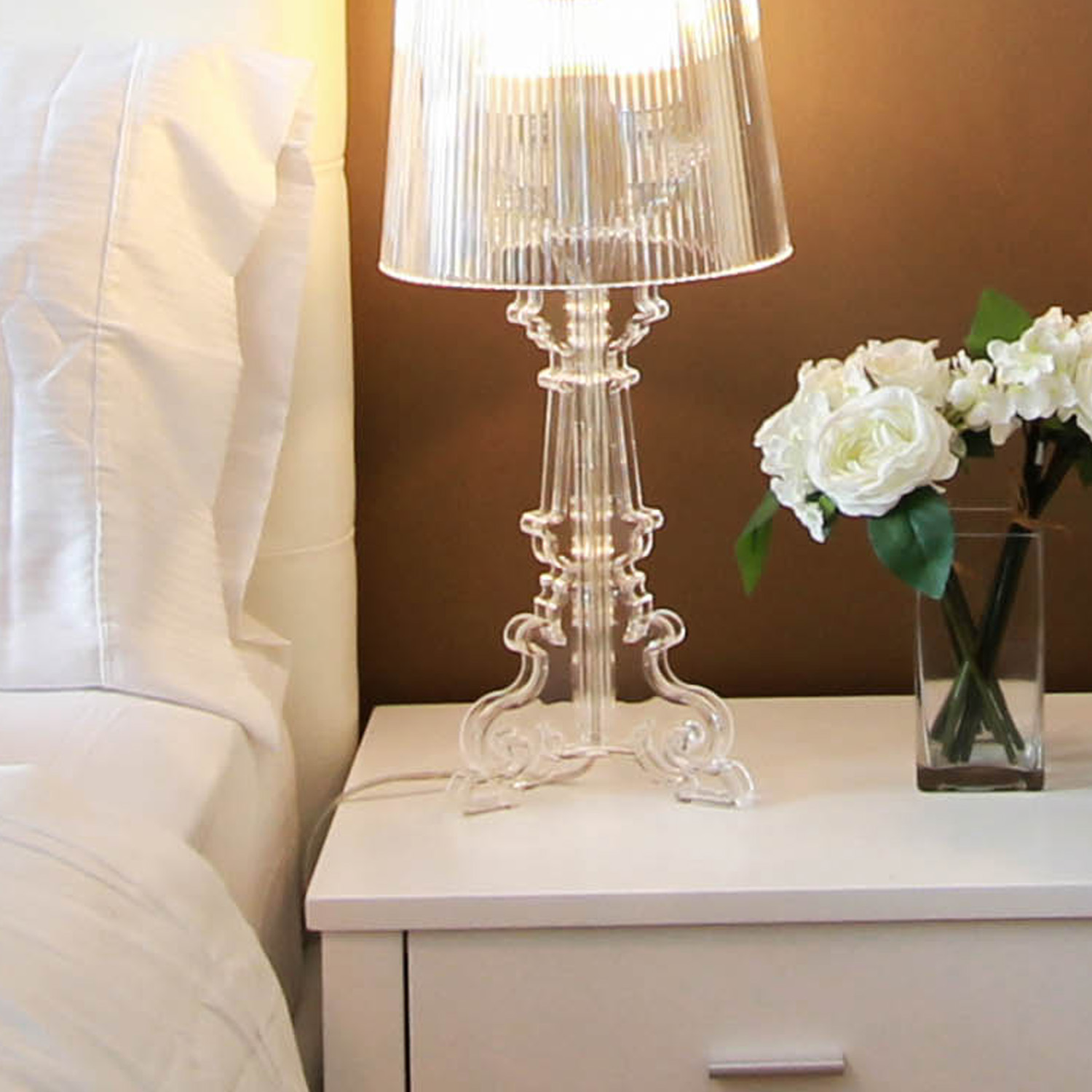Lamp and small vase of flowers on nightstand next to made bed