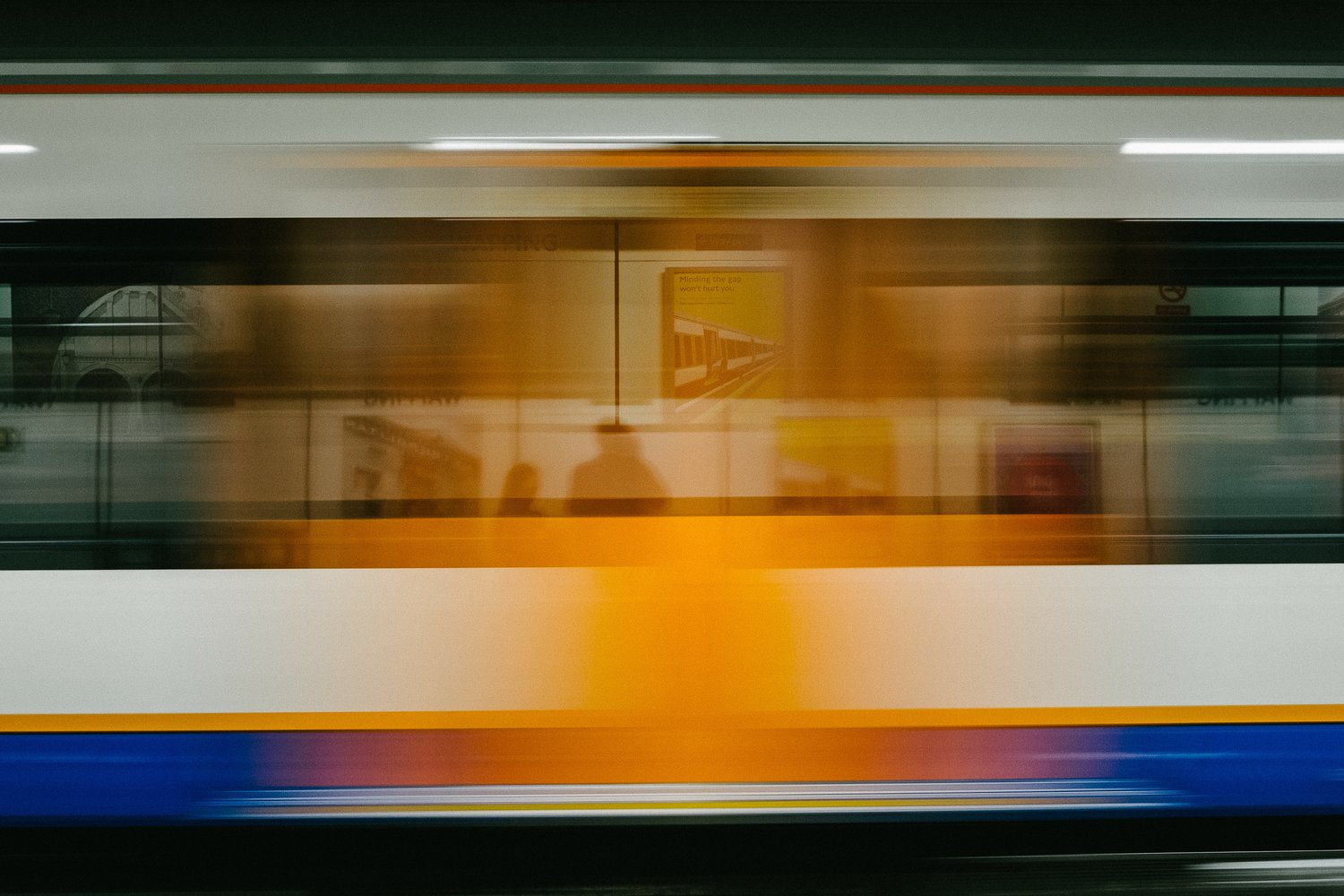 Speed-blurred shot of subway car zooming through station