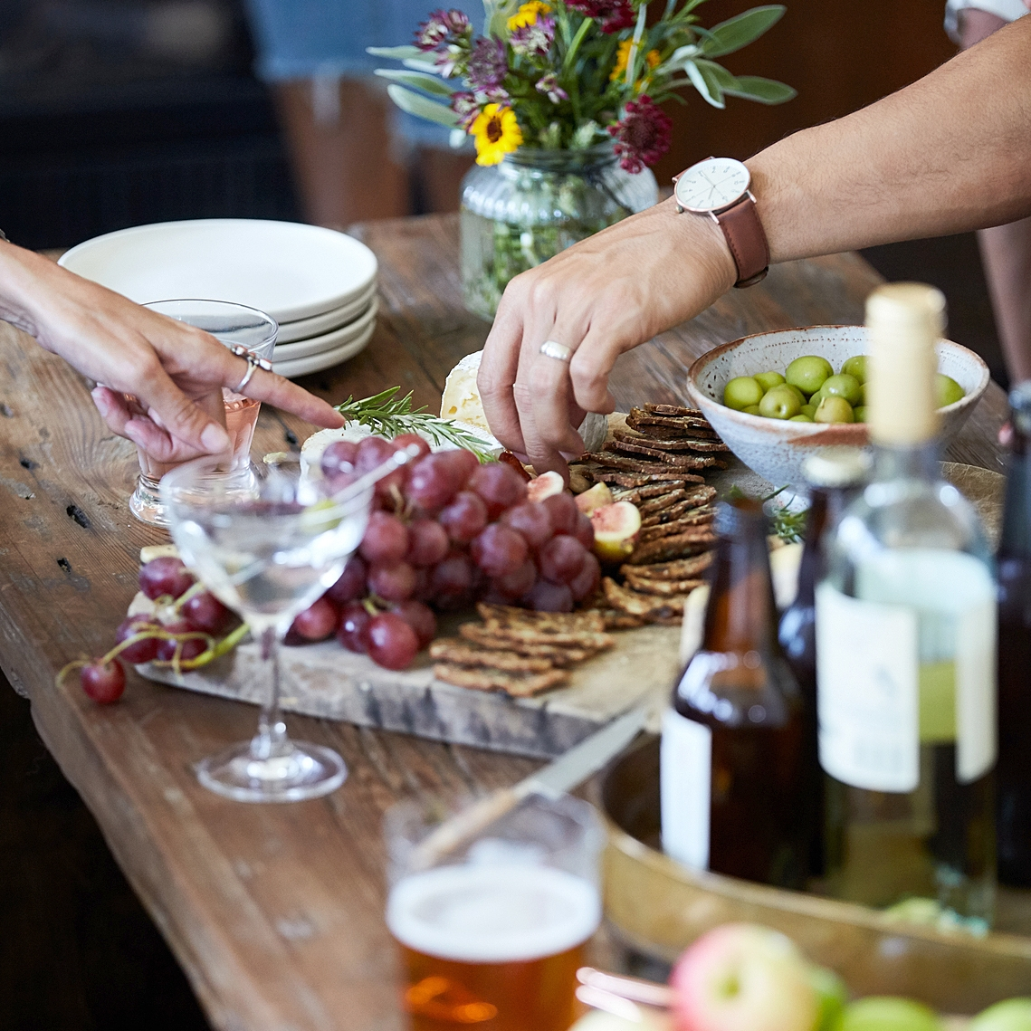 Hands reaching for food and beverage items on outdoor table