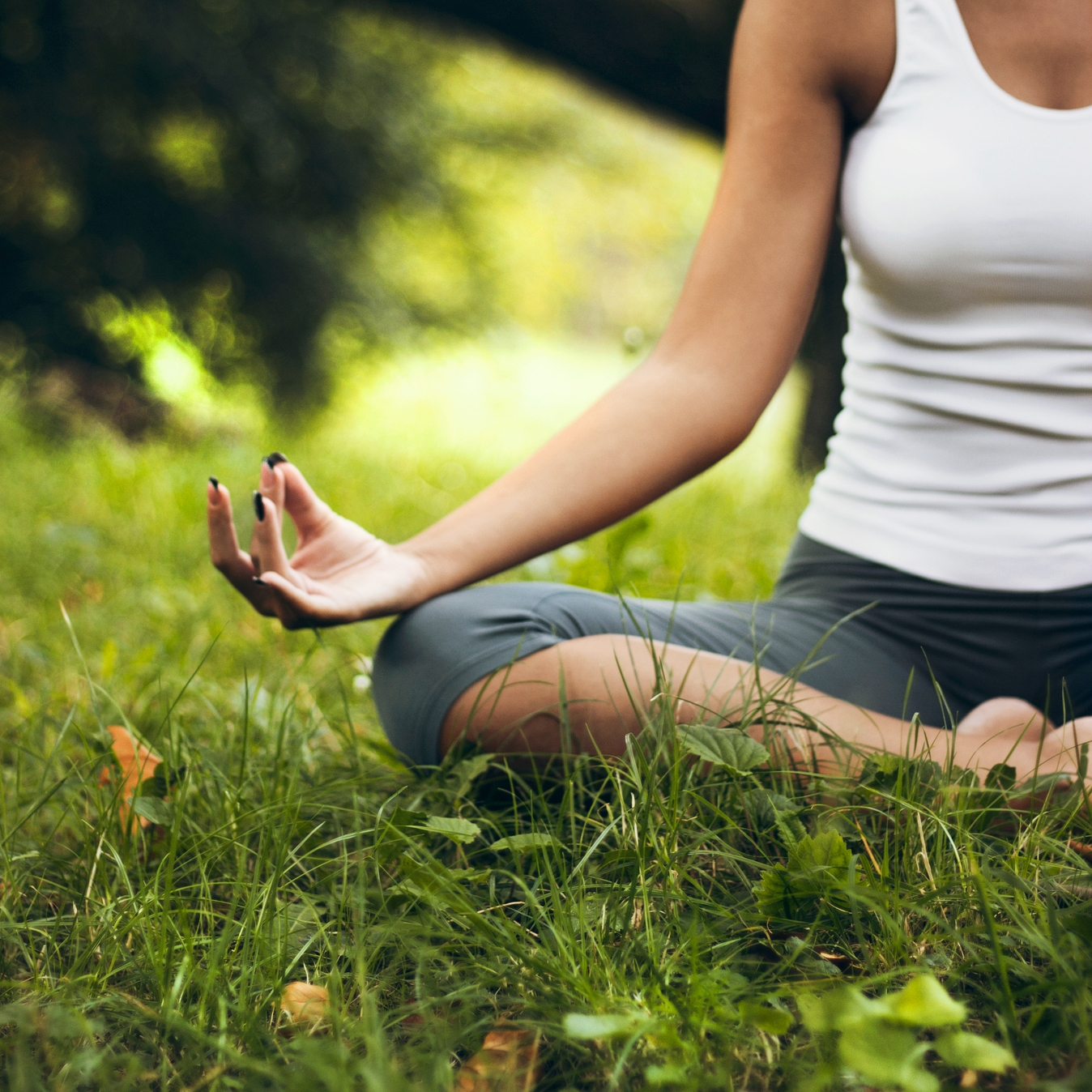 Woman practicing yoga in Lotus position in park