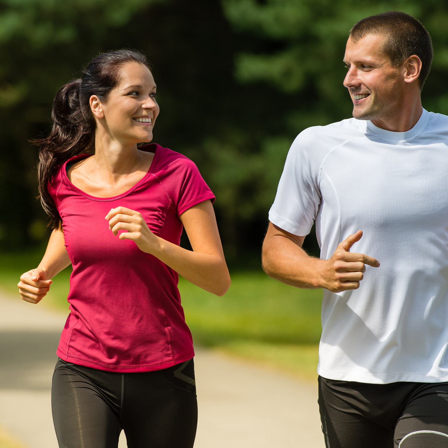 Couple jogging down wooded trail, smiling at each other