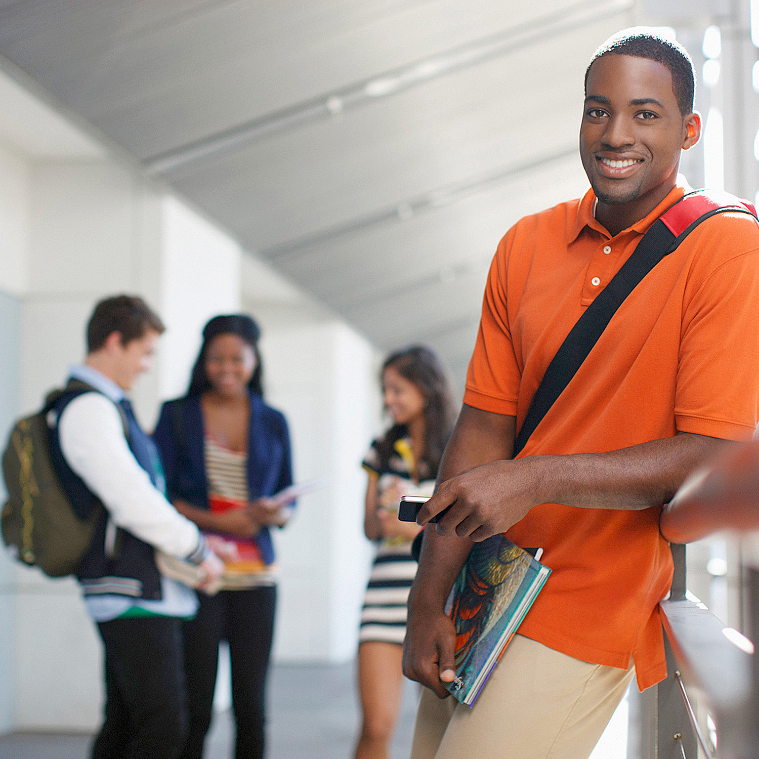 Smiling young man in high school hallway, three other students in background