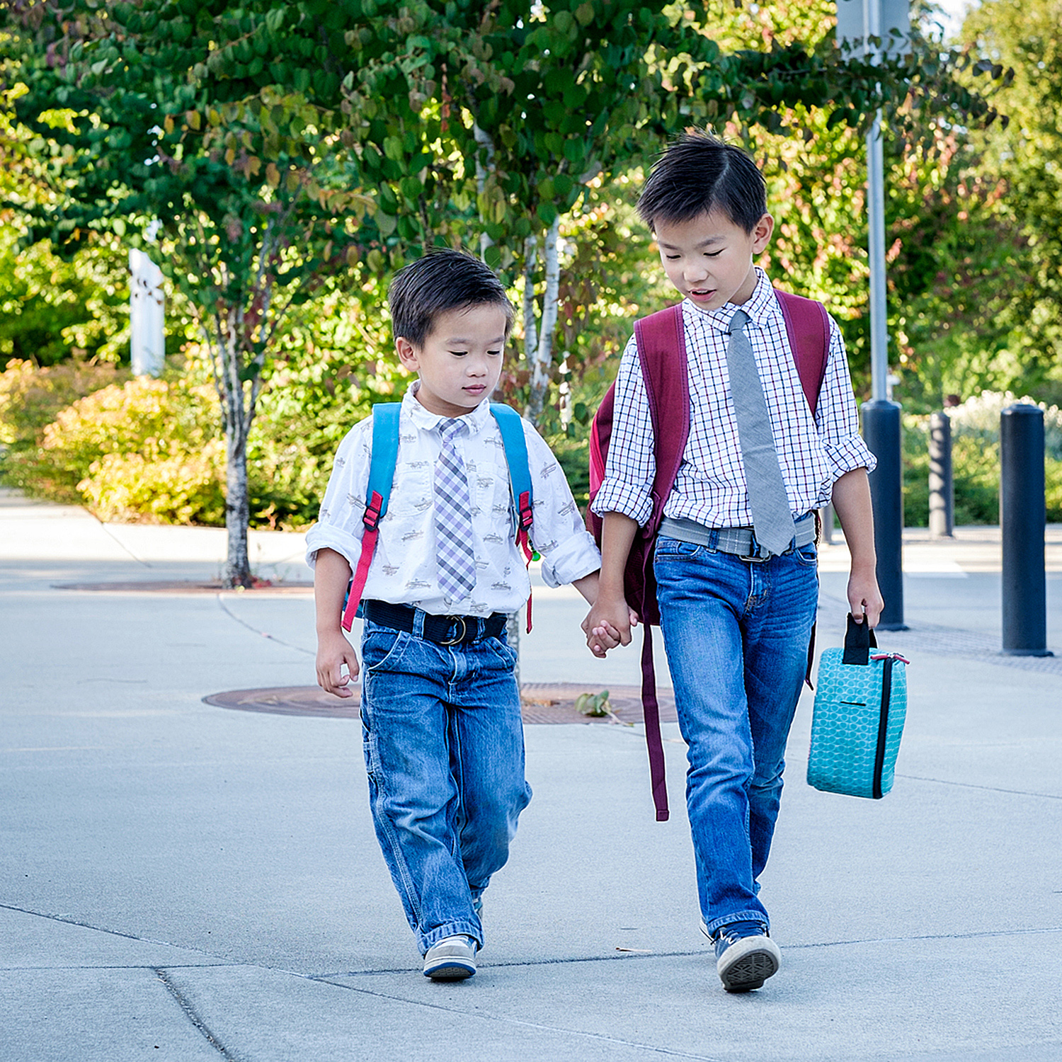 Older brother holding little brother's hand, leading him down the street, both with backpacks