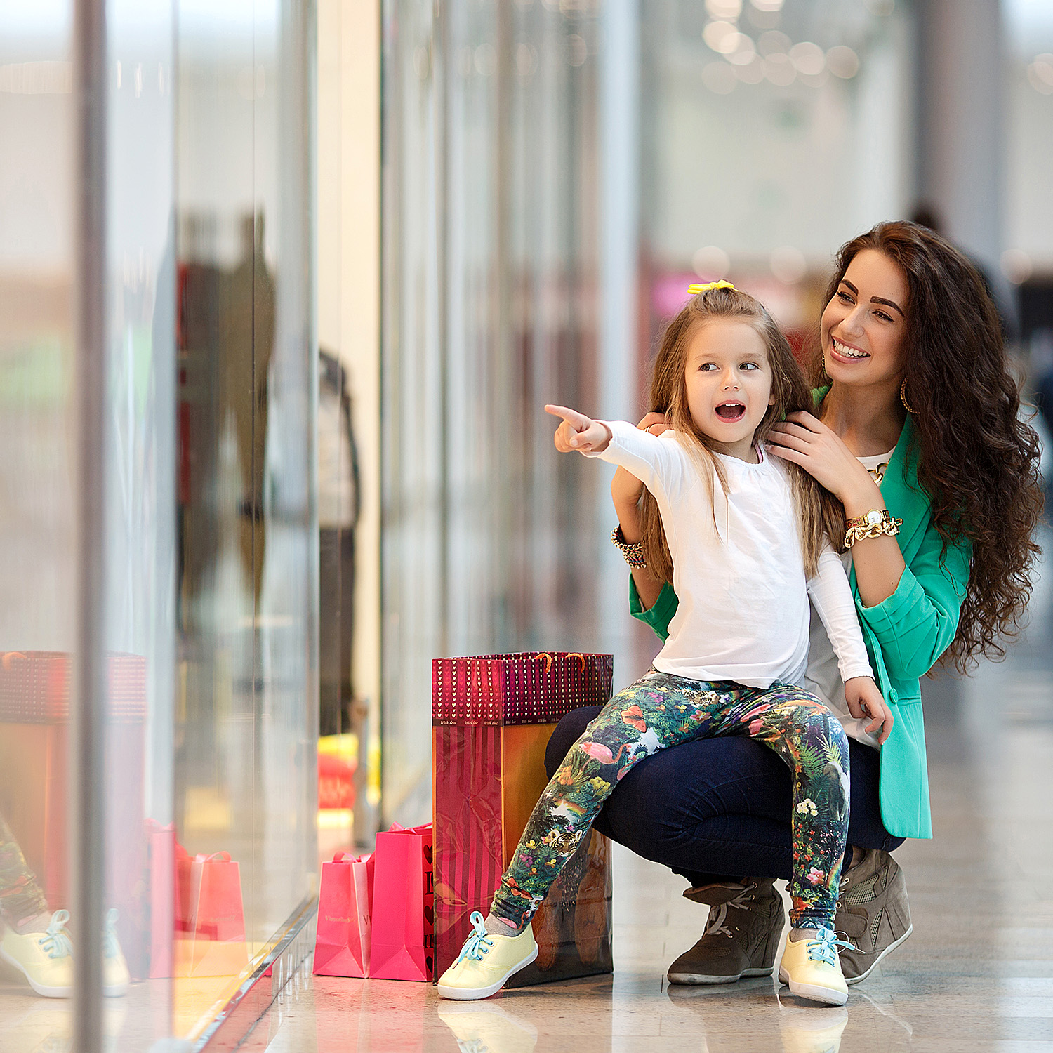 Little girl in mall, pointing excitedly at something she wants her mom to see, mom is kneeling beside her, smiling
