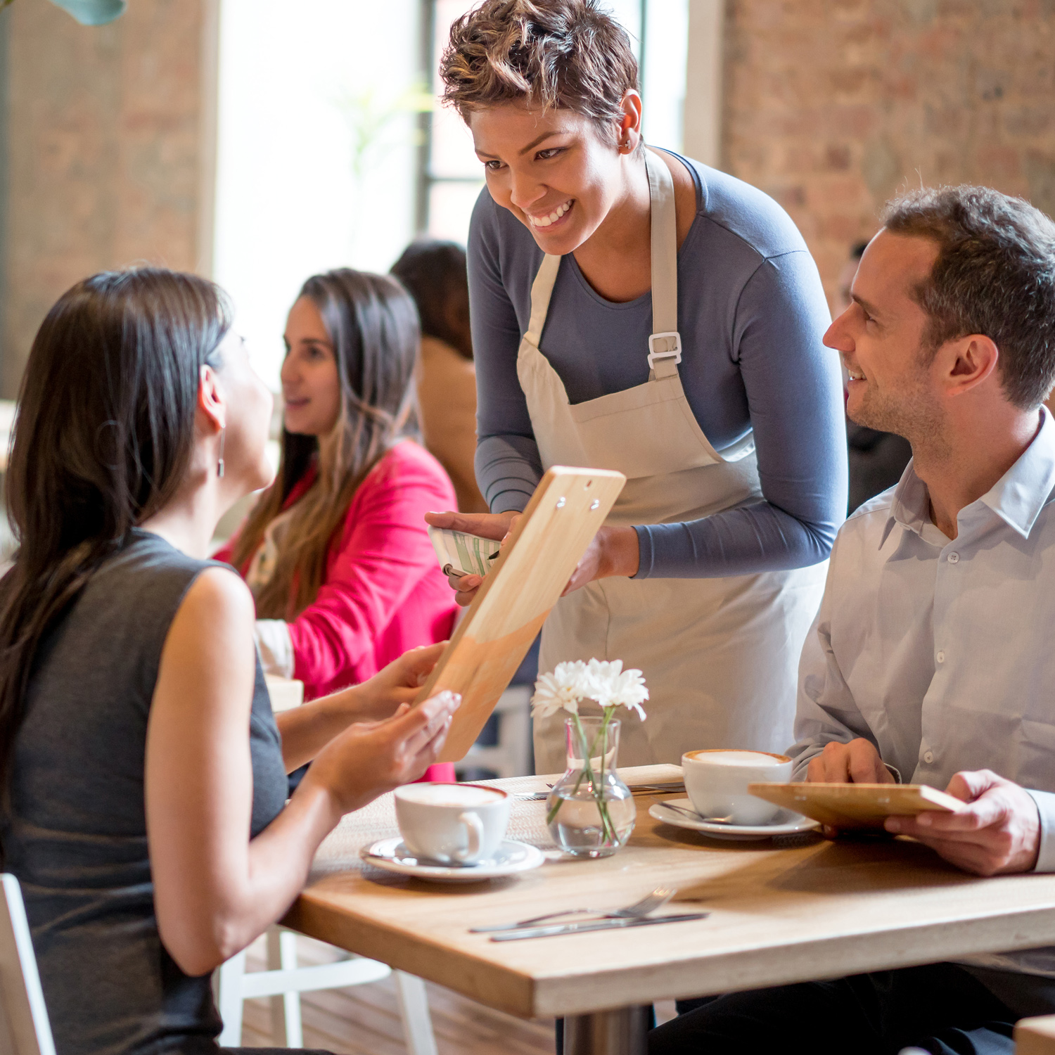 Smiling server taking order from couple at table-for-two in small café