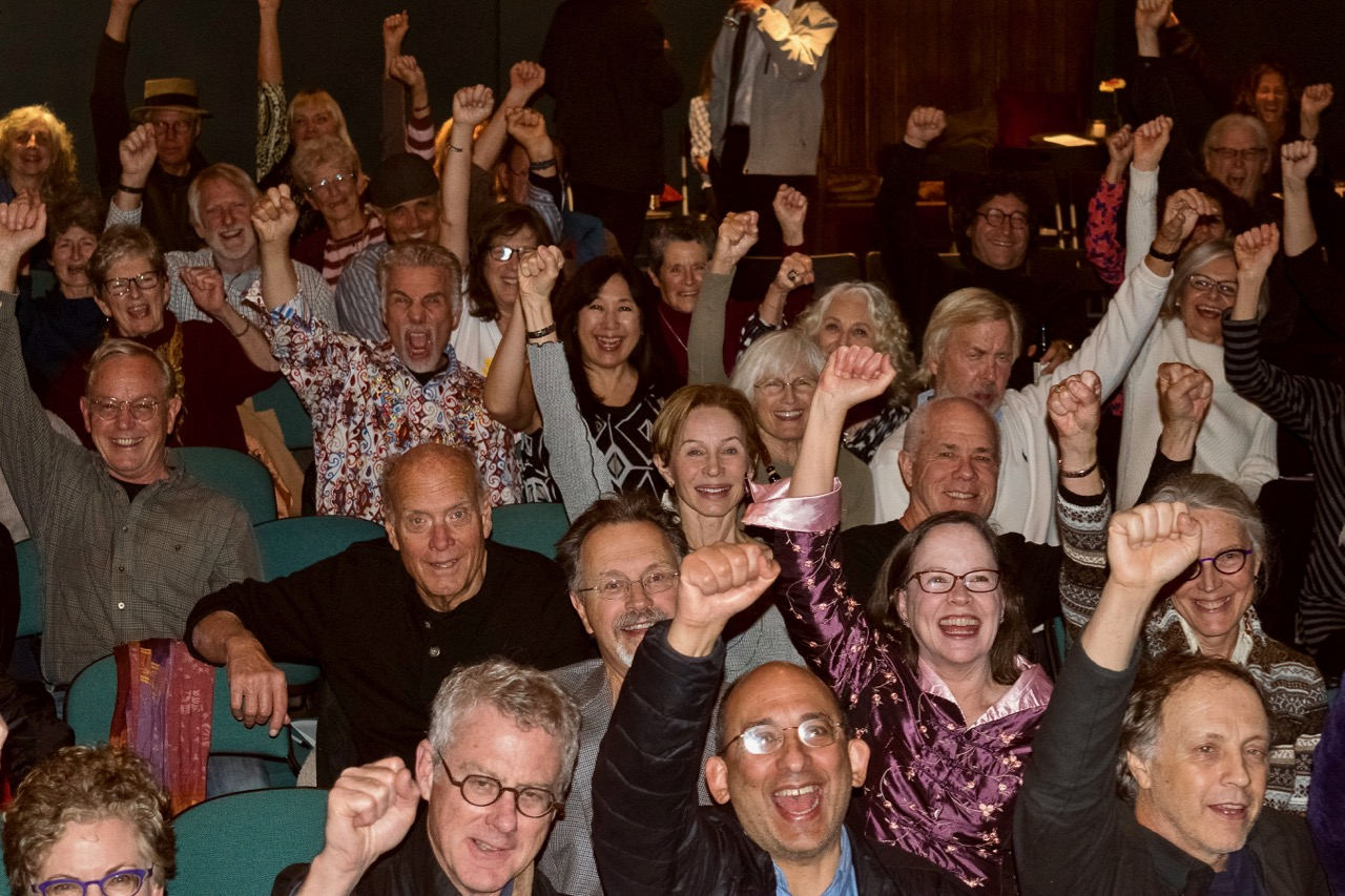 Activists raise their fists for democracy at our MVCAN community celebration. Photo by Martha Ture.