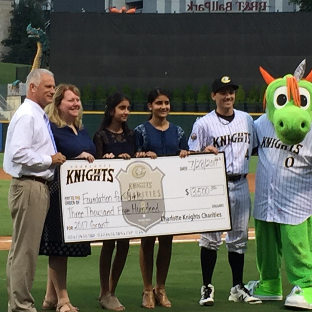 Foundation For Girls Founders Shreya and Sahana Mantha, and Program Leader Liz Mockler accept a grant from Charlotte Knights Charities.