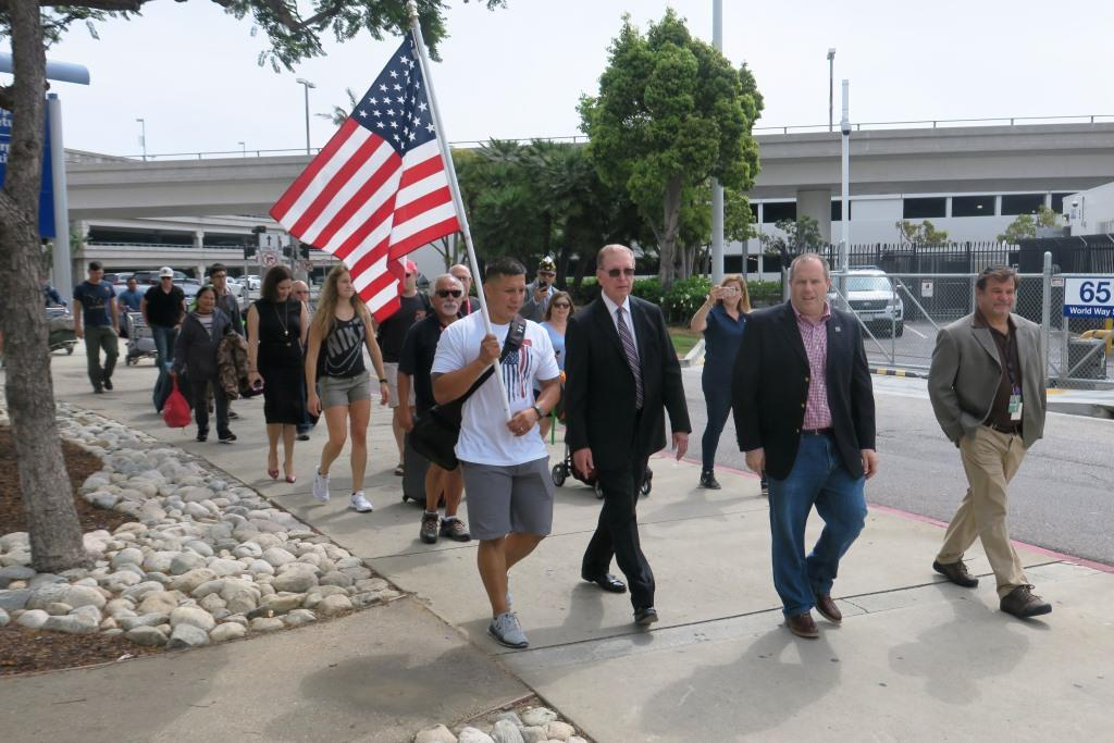 A flag bearer helped guide the first arrivals from the former USO location to the Theme Building.