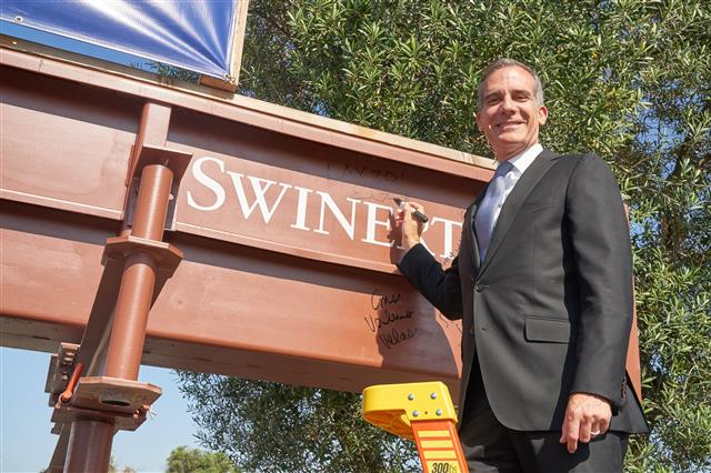 Mayor Eric Garcetti signs a beam at the event, which will be incorporated in the future structure.