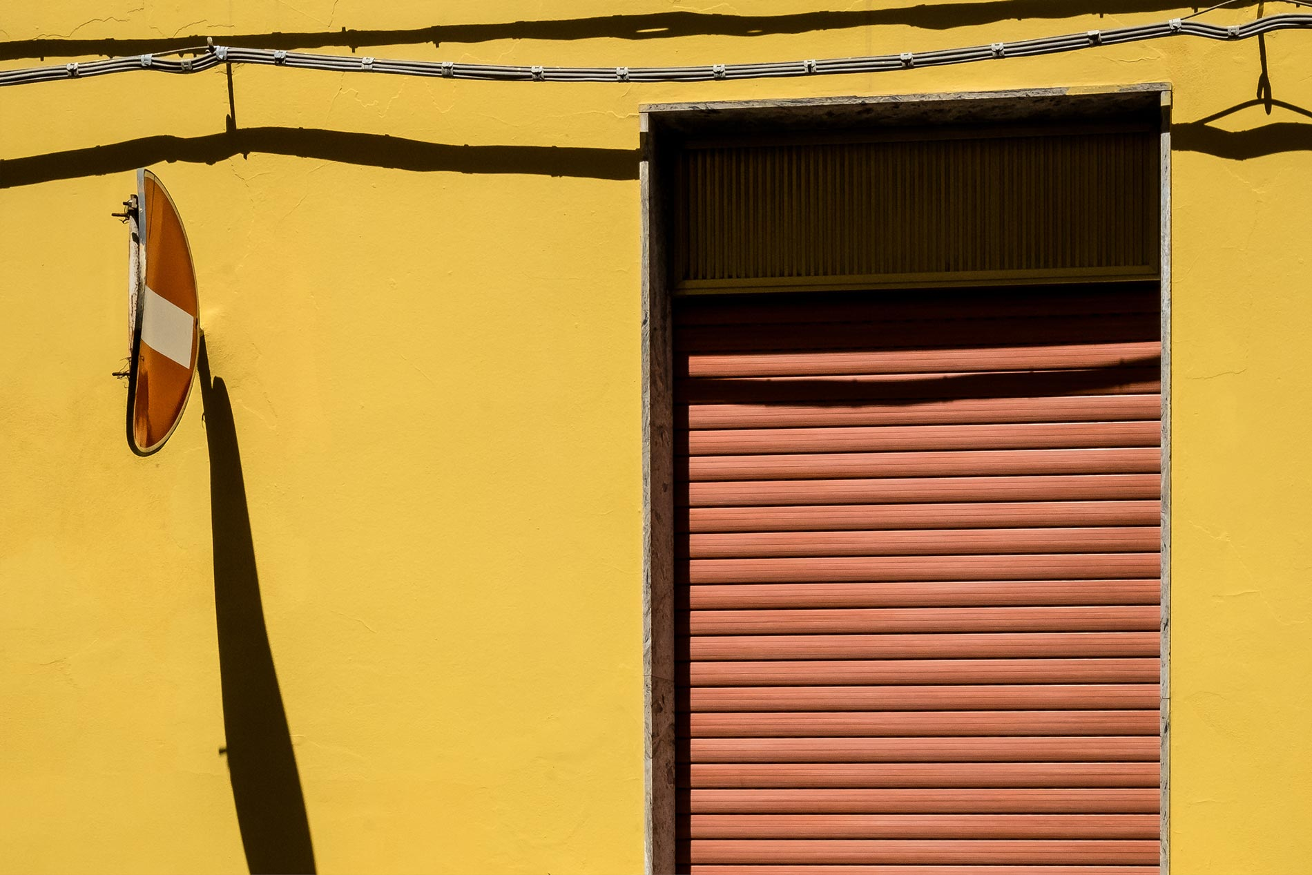 Yellow wall and sign - Floridia, Sicily