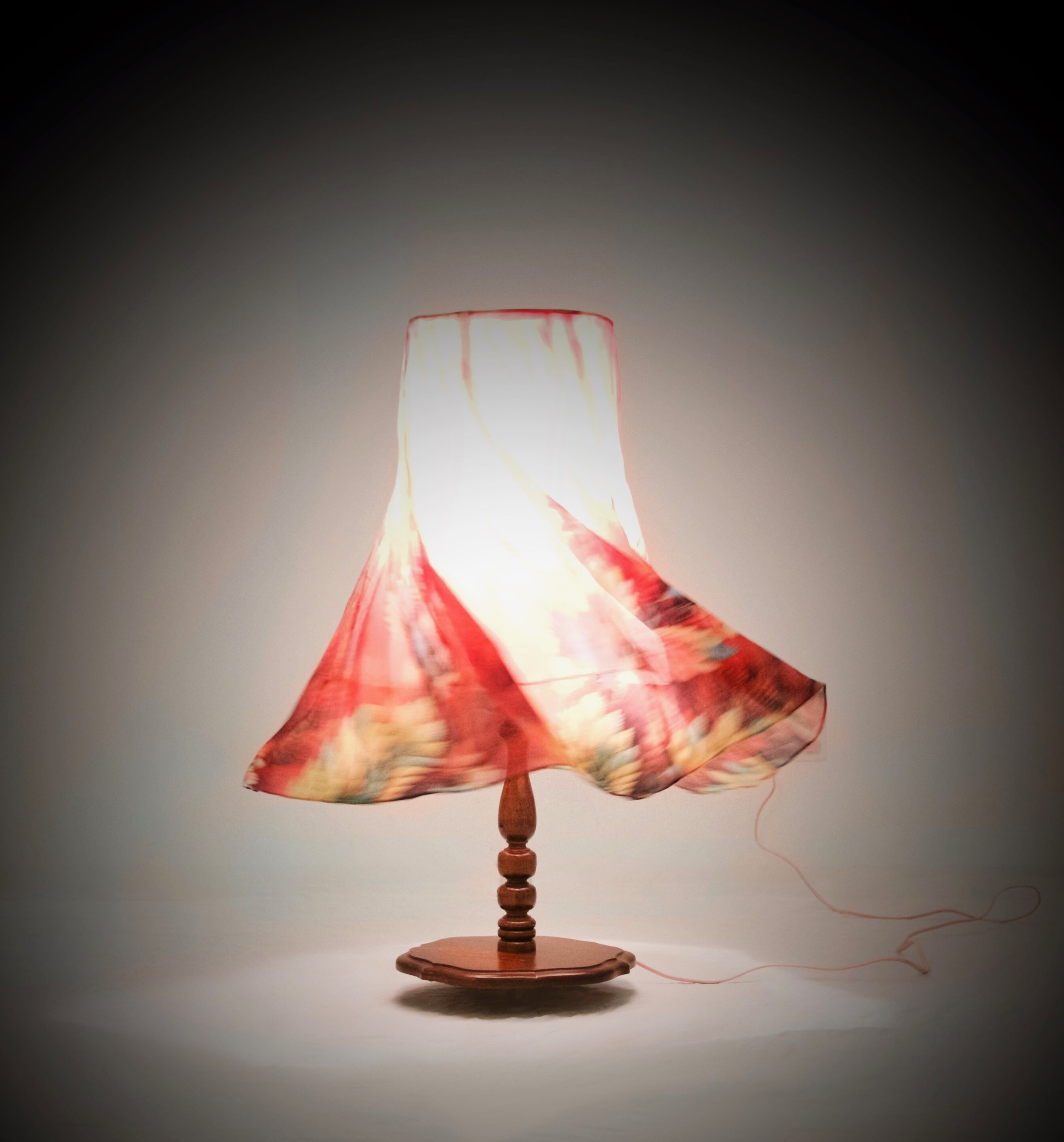 "She Dances Like a Bomb   44"" x 13"" x 13"" - when stationary  1970's side-table lamp, Edison light bulb, Arduino, 24v motor, tropical print skirt, floral scent  (2018)"