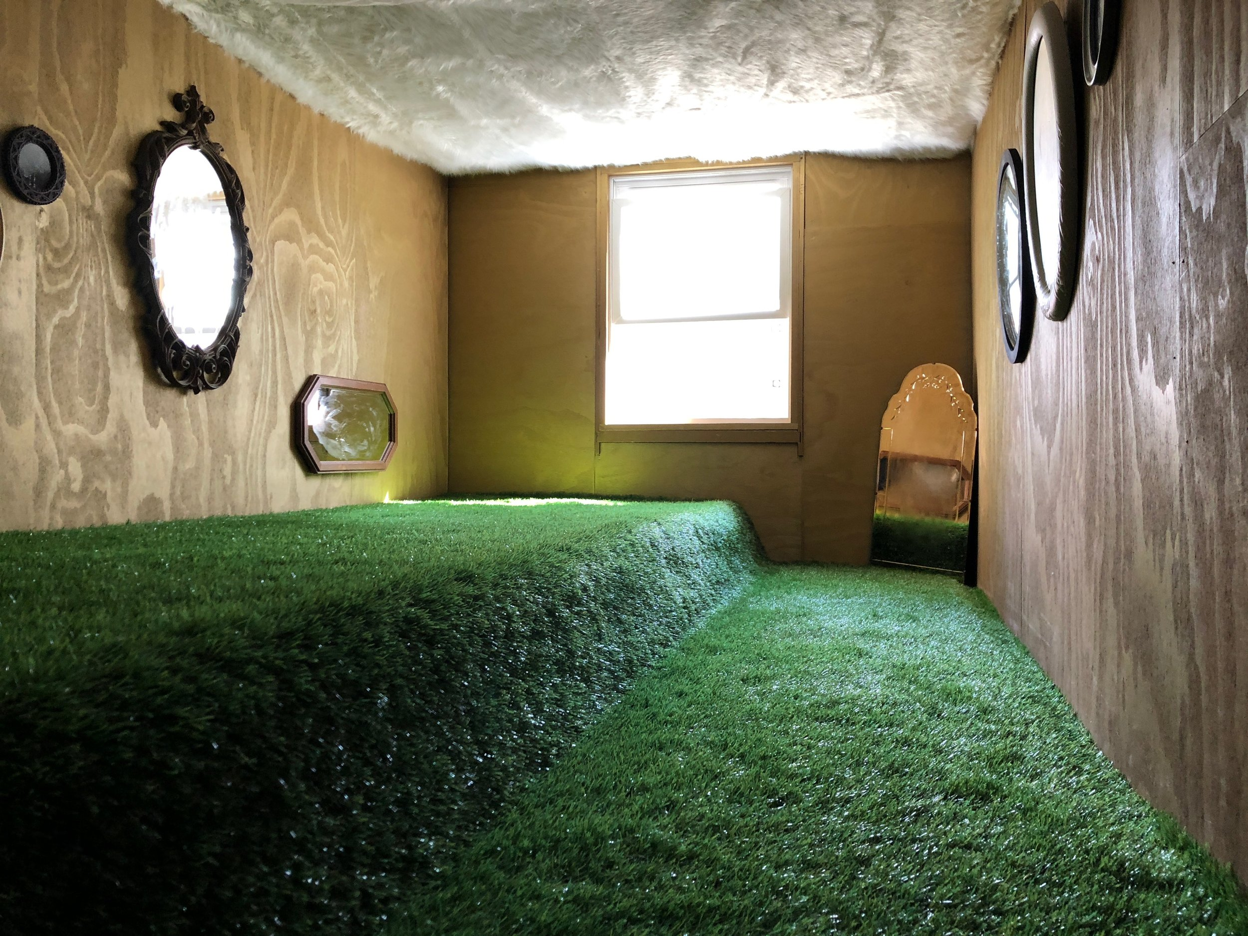 "Golden Attic aka Grandma's Jersey House, 1985   132"" x 60"" x 108""  Golden wood panels, plastic grass, fur clouds, scrying mirrors, scent of wet dirt  (2018)"