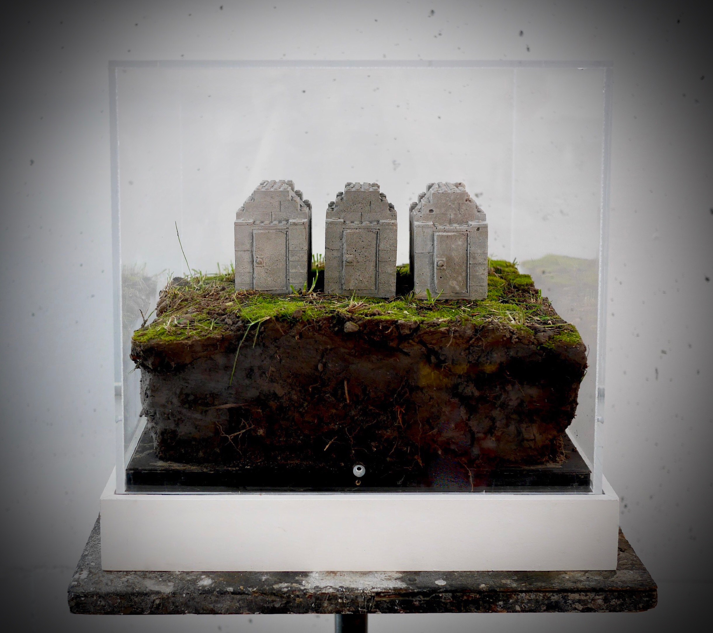 "You Can Have 3 Wishes While the Ground Still Stands   15"" x 15"" x 15""  Cast concrete lego houses, patch of Iowa ground, plexiglass case  (2017)"