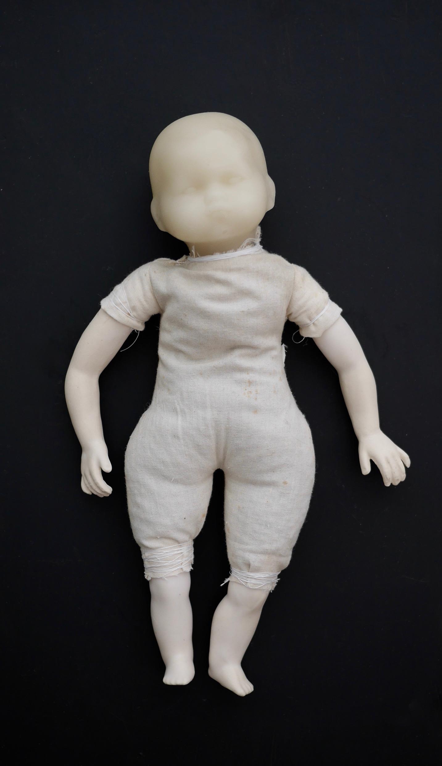 """Doll Baby, Wax   12"""" x 8"""" x 3.5""""  Cast wax, found fabric, lentils  (2017)"""