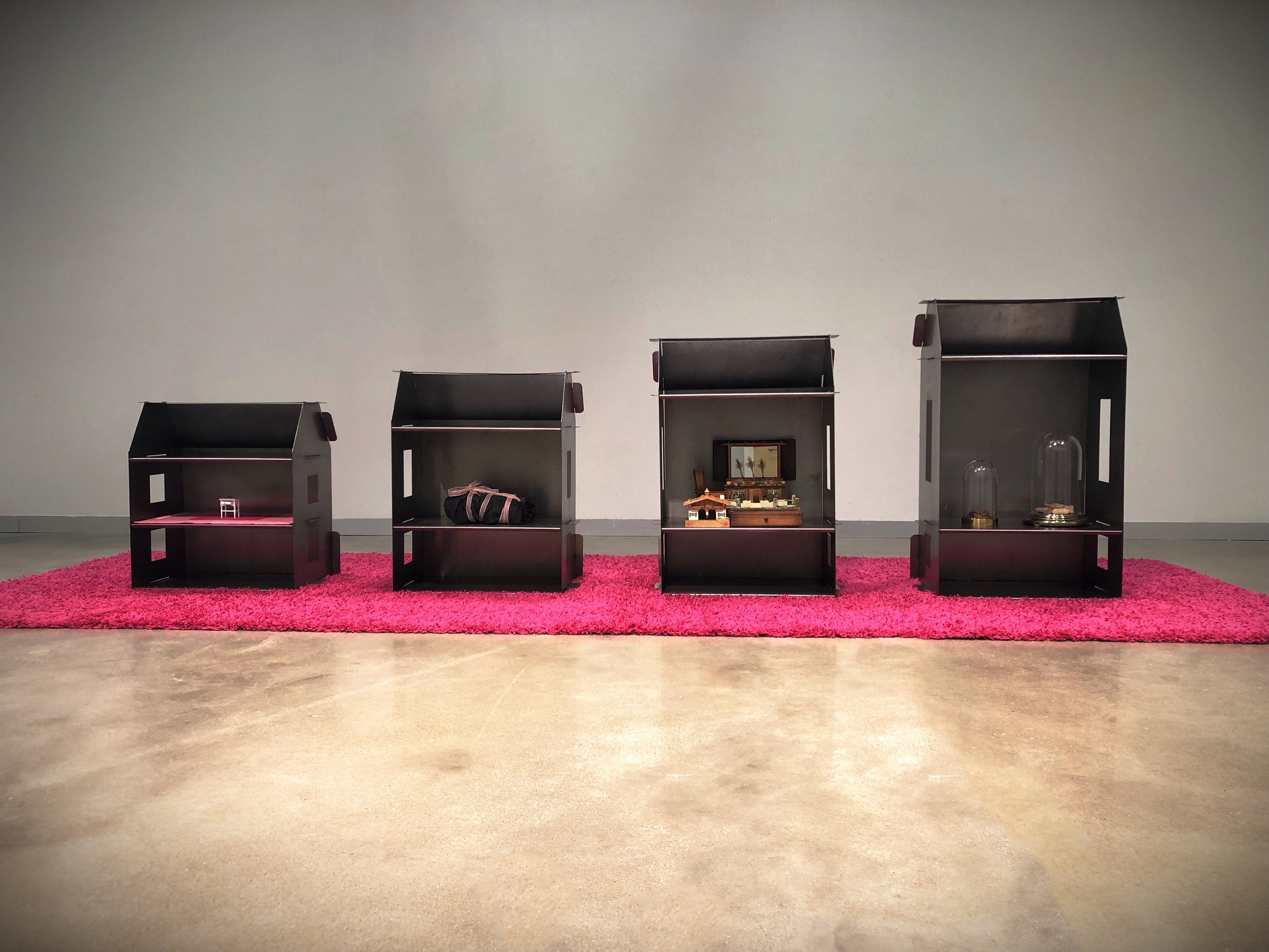 """Ghost House Series   48"""" x 154"""" x 54""""  28 slotted steel pieces (Non-welded), 2 hot pink shag rugs, dollhouse furniture, felt, black dress, pink sparkle ribbon, house shaped music box, minature wood house, 2 lbs dried cloves, 2 cloches, hair from my mother, 9 rocks from rural Nebraska, light scent of goldenrod  (2019)"""