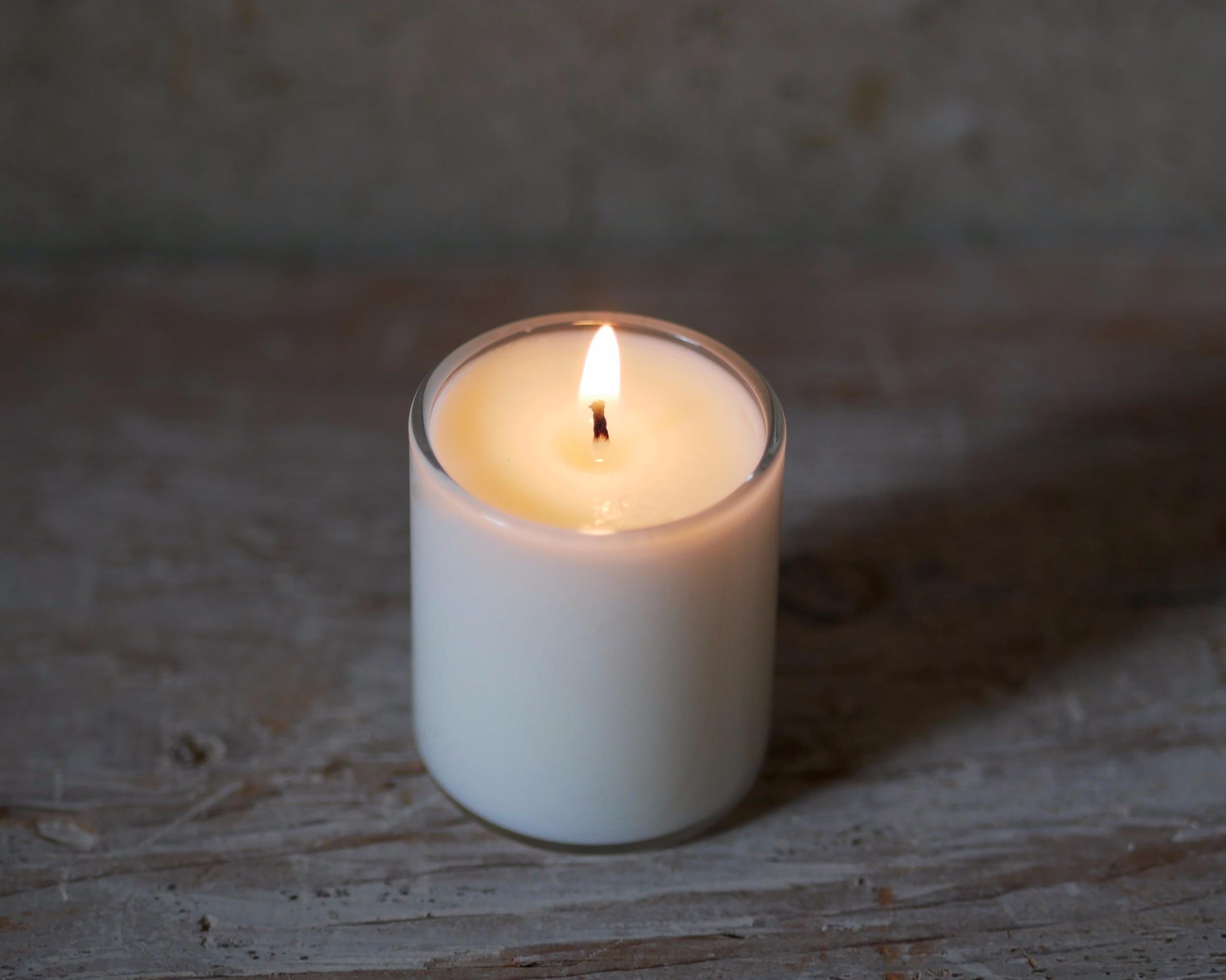 The warm glow of a lit E+A votive candle