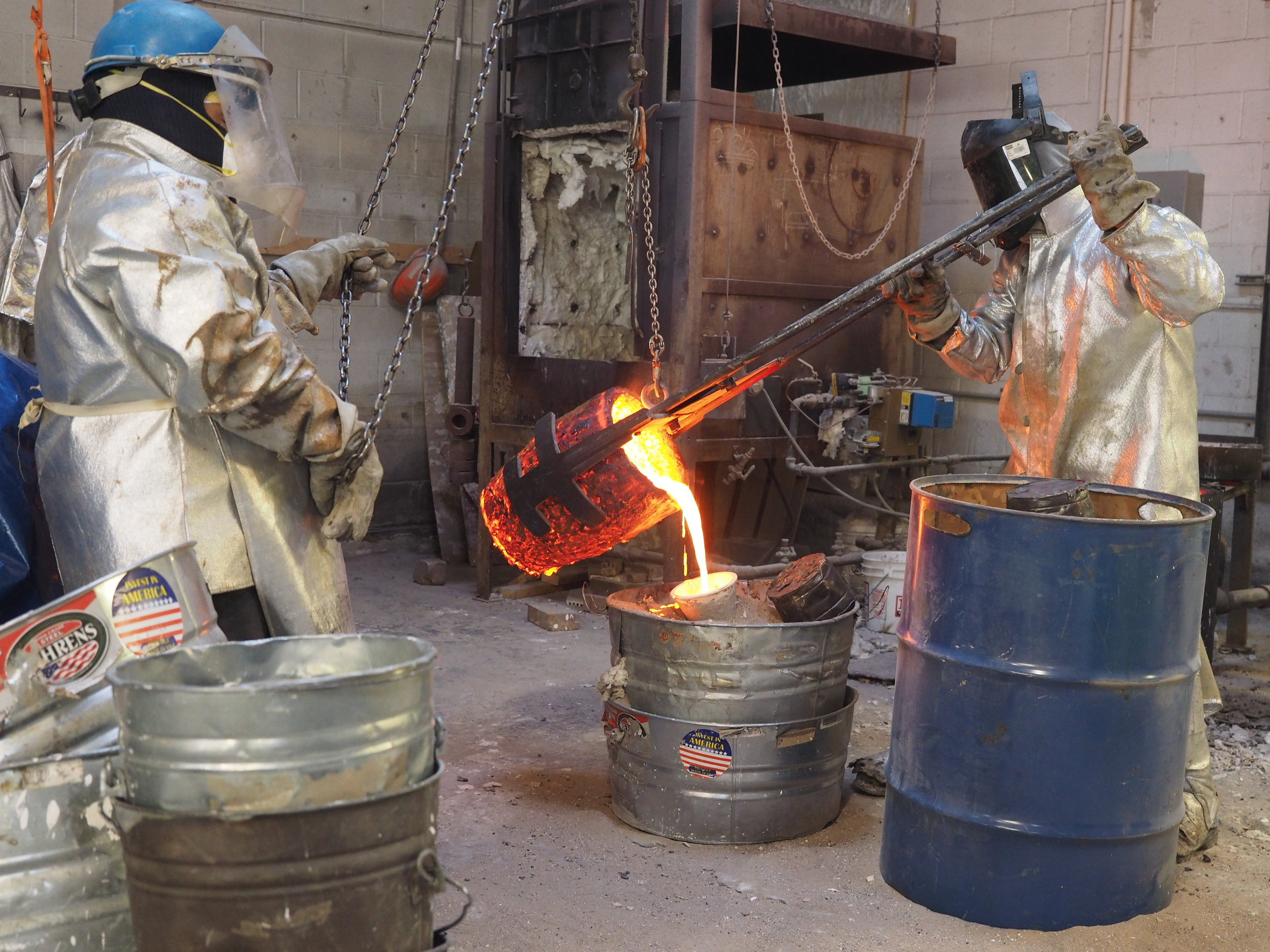 Molten bronze being poured into prepared ceramic shell mold.