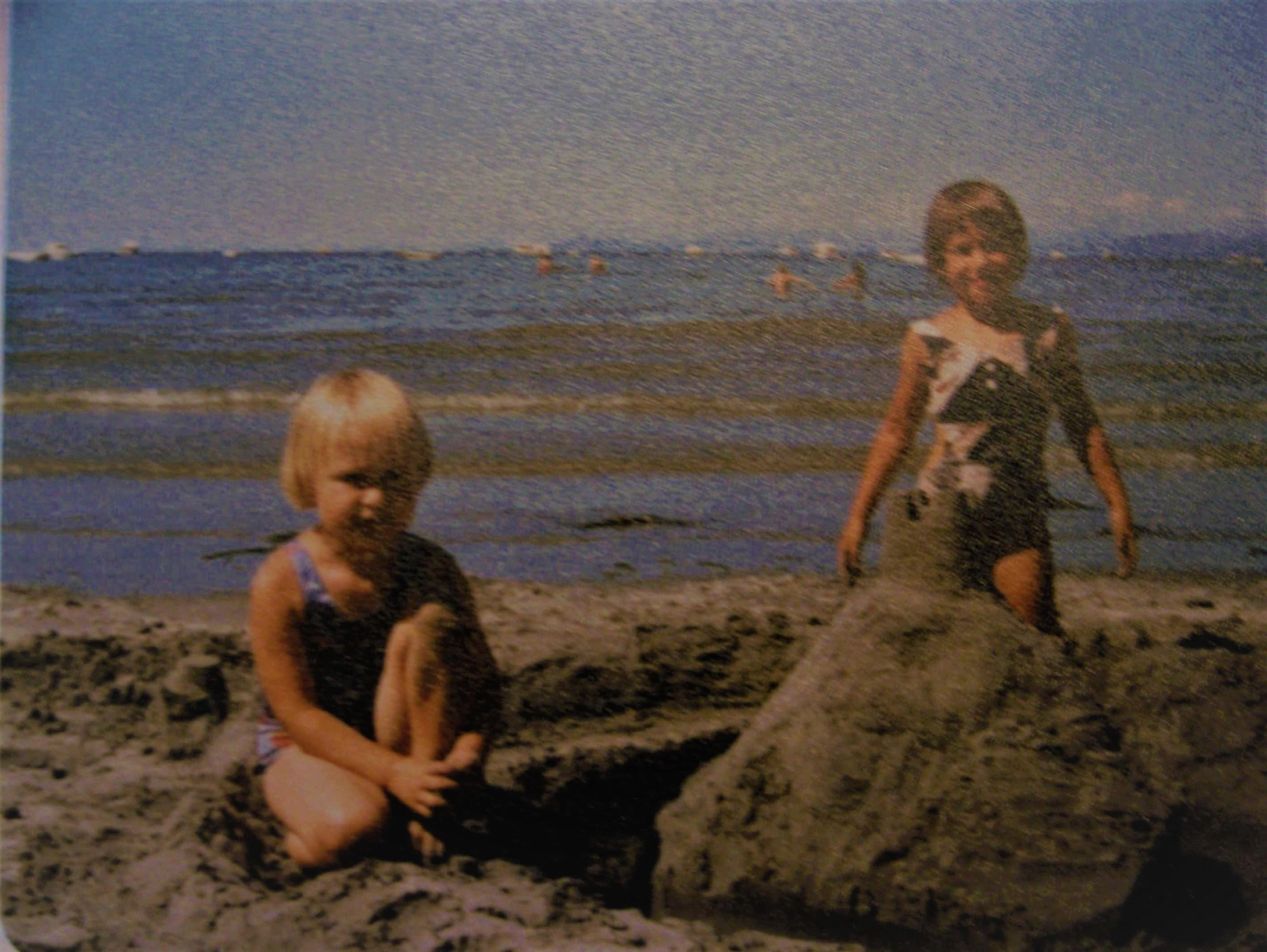 My sister and I playing on the beach near our home