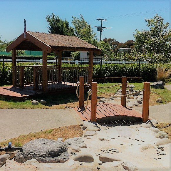 The new water play area/river bed, bridge and hut before the planting