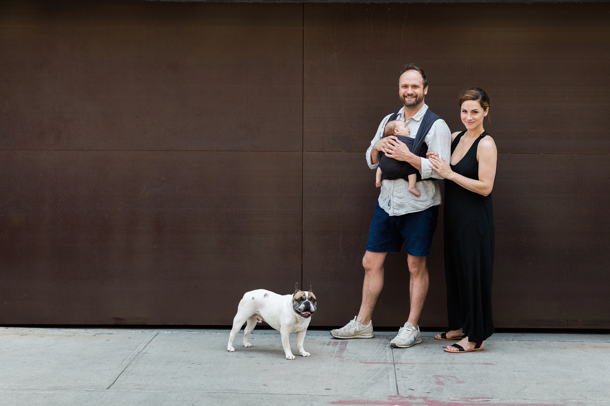 Family poses for a portrait with their dog in dumbo brooklyn