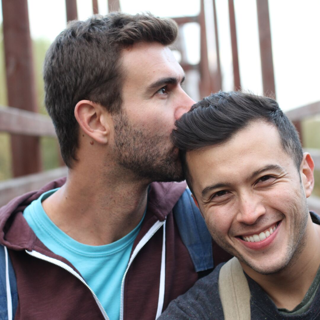 Gay male couple kissing head on bridge.png