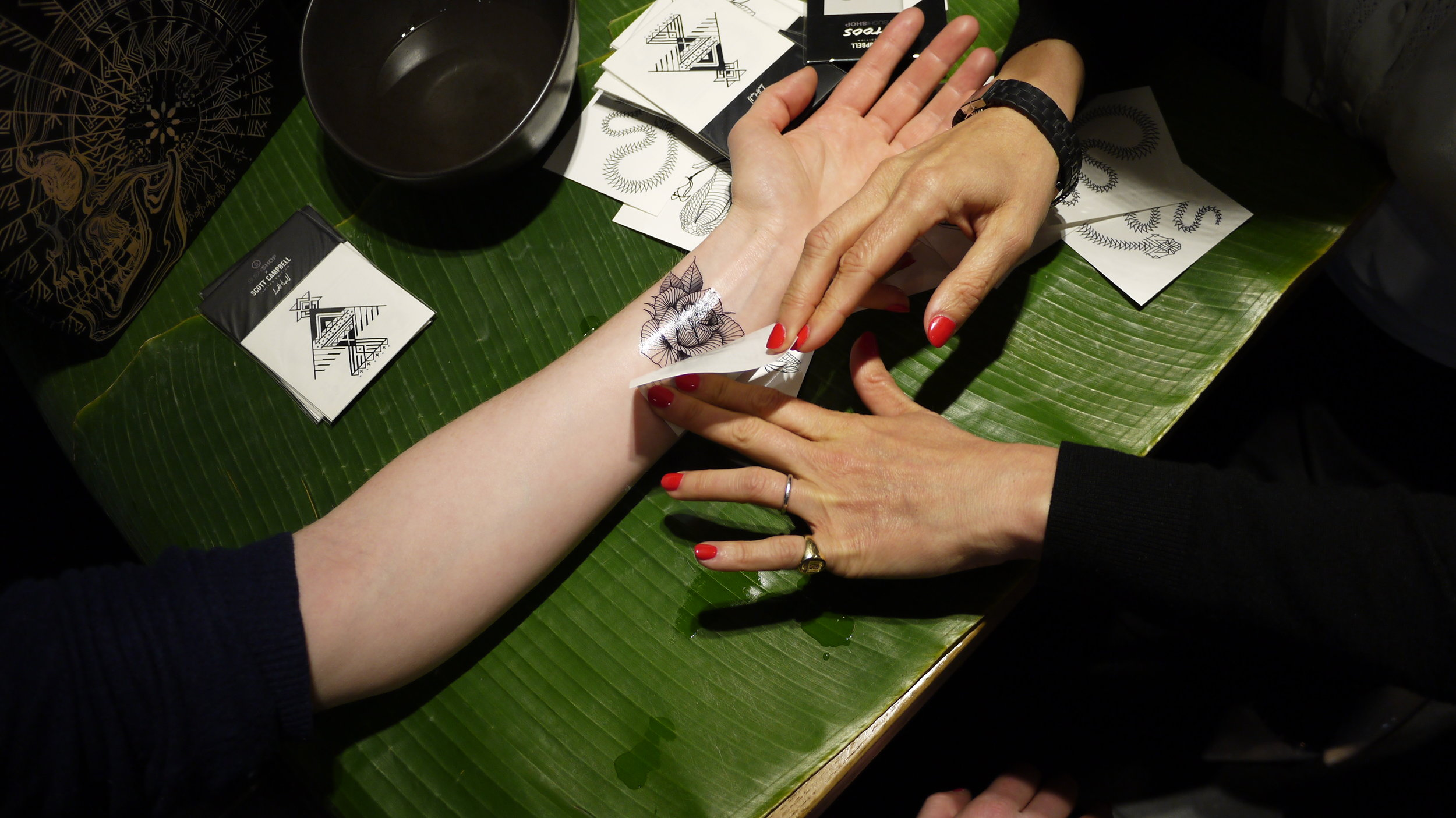 Scott Campbell temporary tattoos being applied at the Sushi Shop event