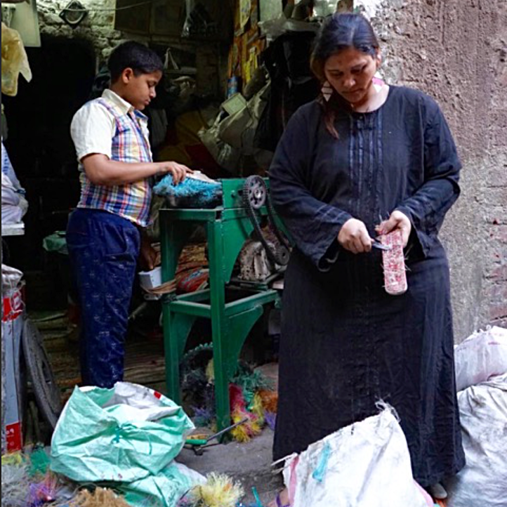 Mariam* bought discarded brooms and invested in a bristle-removing machine which her son is demonstrating. She then trims up the hard plastic base pieces which are valuable for recycling.